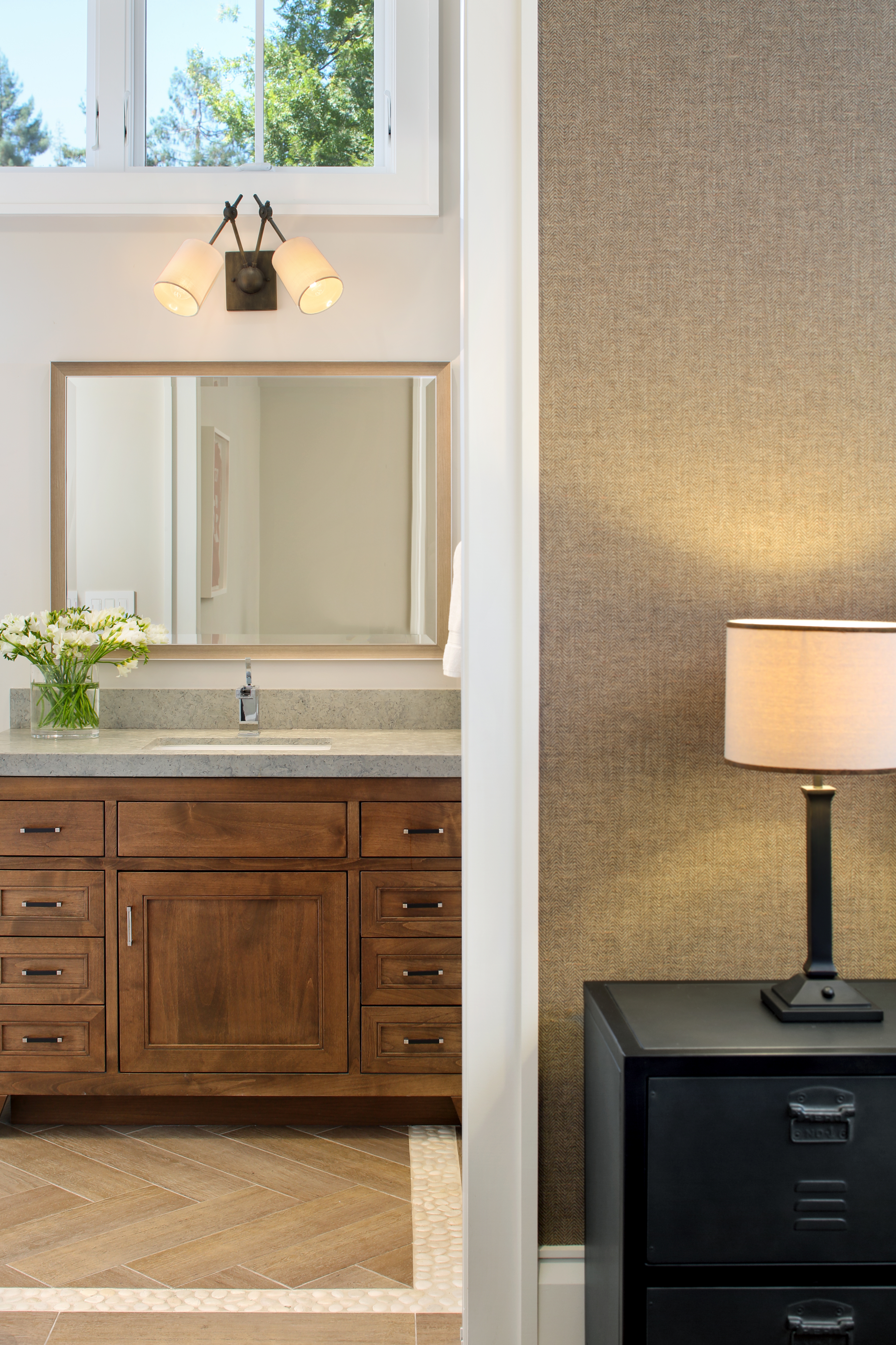 Enter the adjoining bathroom, which features stylish neutrals and an abundance of natural light. Atop the wood vanity is a slab fromBenjamin Gray.