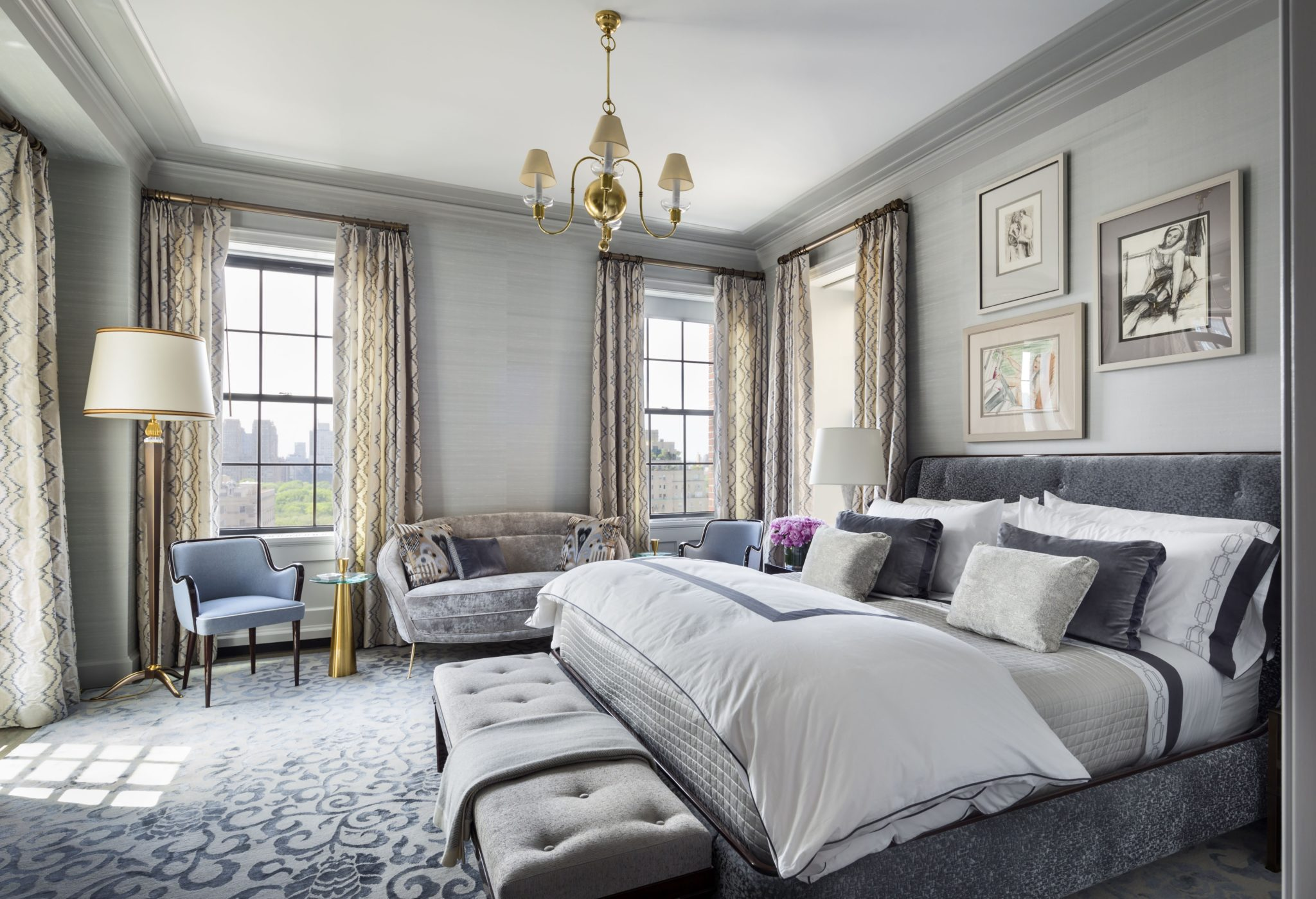The enlarged master bedroom features silk wall coverings by Holland & Sherry, Duralee fabric curtains, and a custom-made side table by The Lacquer Company. The rug was also custom-made by Mansour Modern.