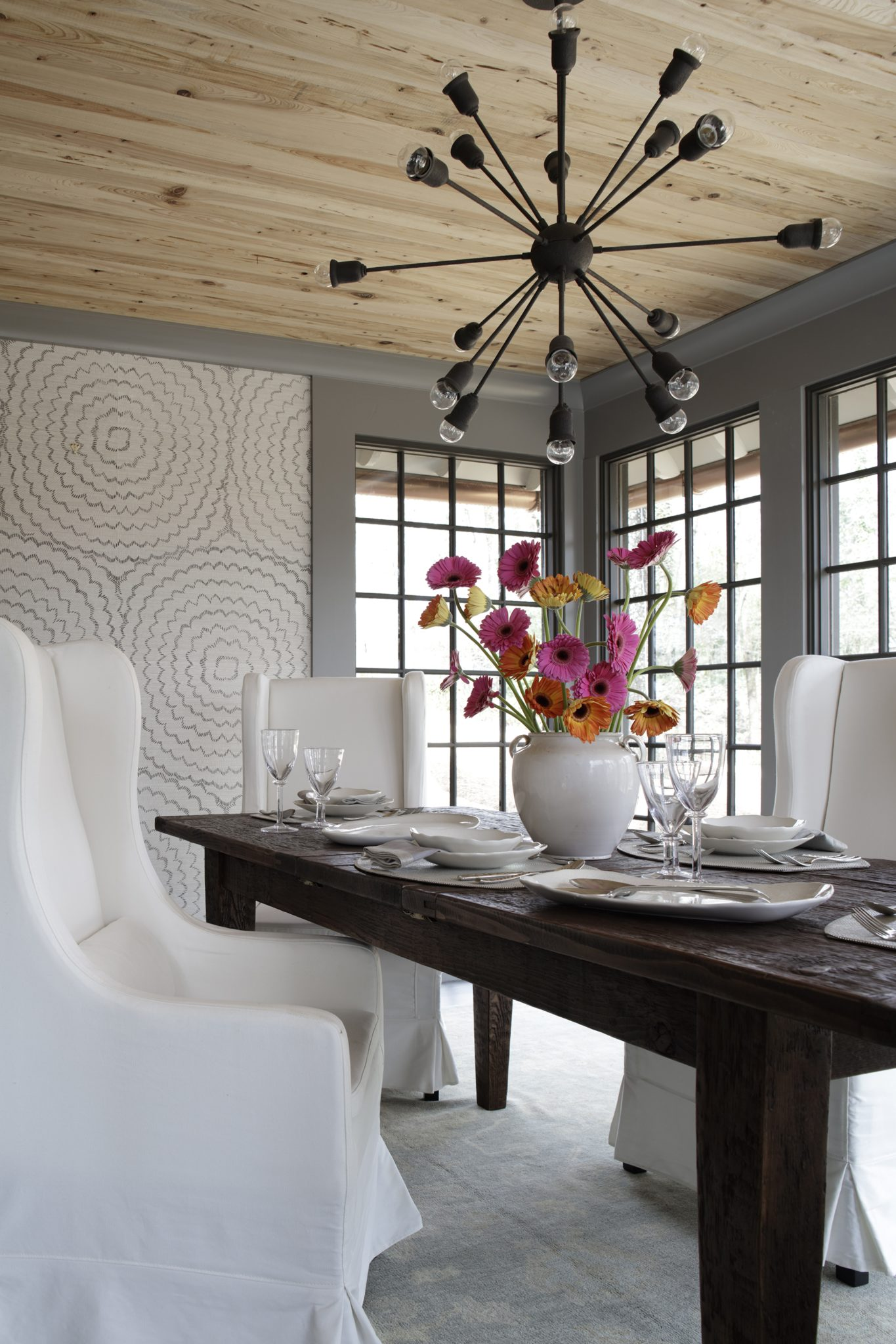 The dining room is creatively elegant, featuring a floral Schumacher wallcovering that accents the space. The table is an antique from Argent Antiques in Homewood, Alabama; the chairs are also from Argent Antiques, and the chandelier is from Currey & Company.