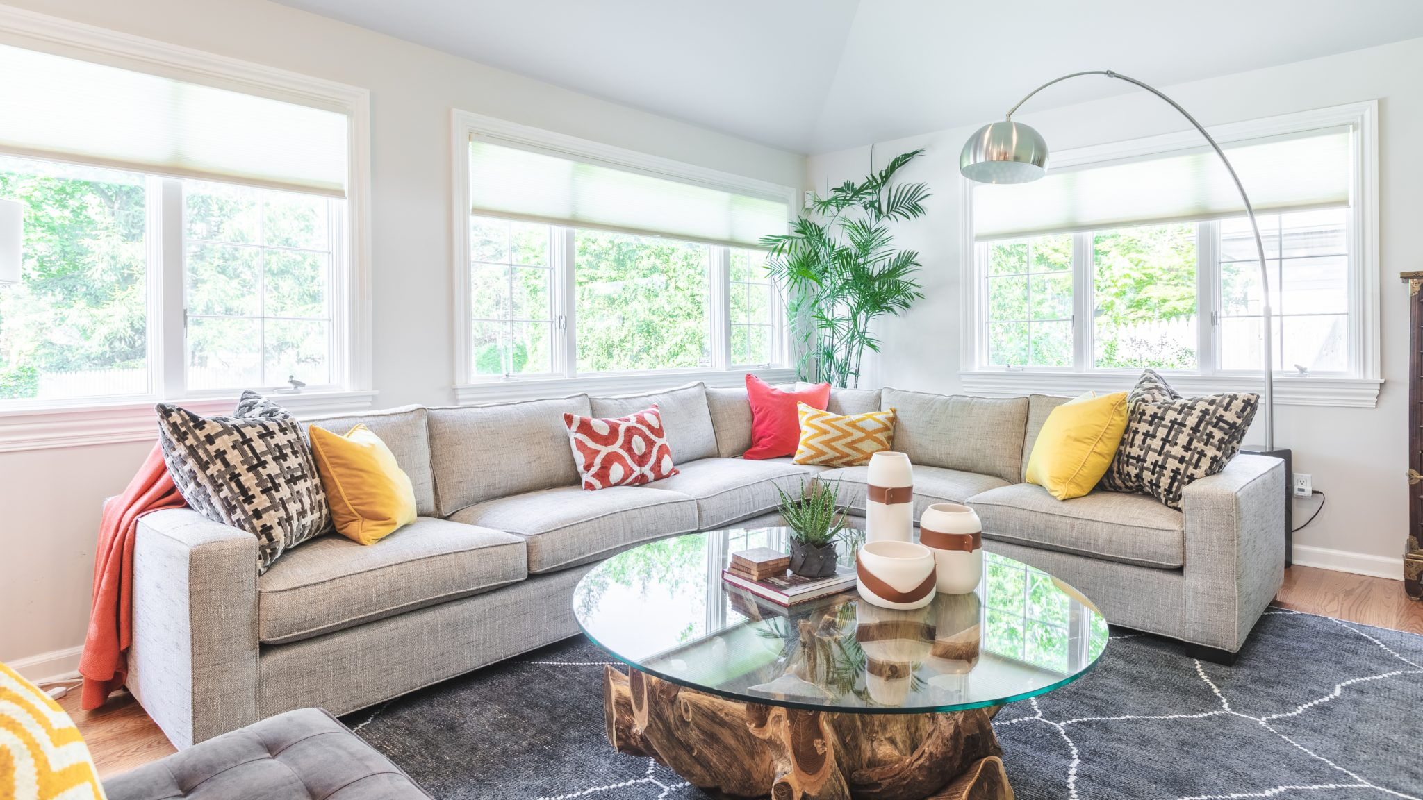 A round glass coffee table with organic wood base provides a focal point. by Shelley Cekirge Interiors