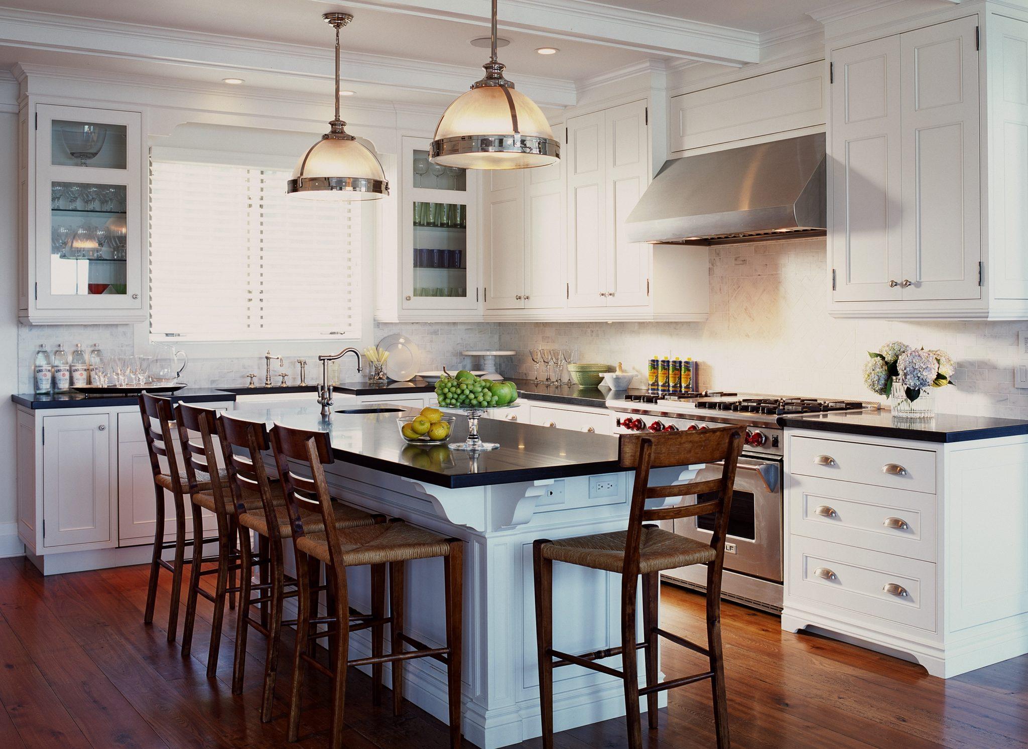 A pristine white kitchen with a large island by Jennifer Worts Design
