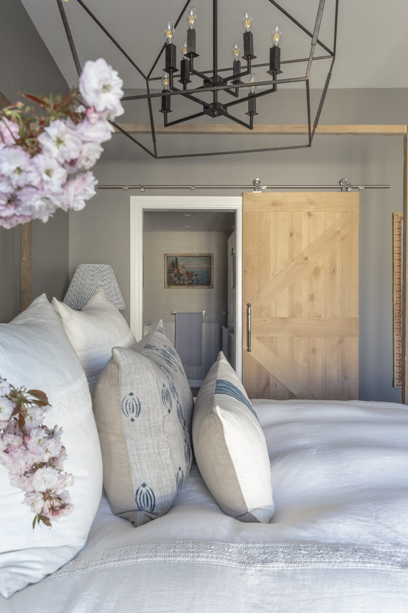 Over sized pendant light and an unfinished barn door are key elements in this casual but luxe master retreat by Bronwyn Poole by Touch Interiors