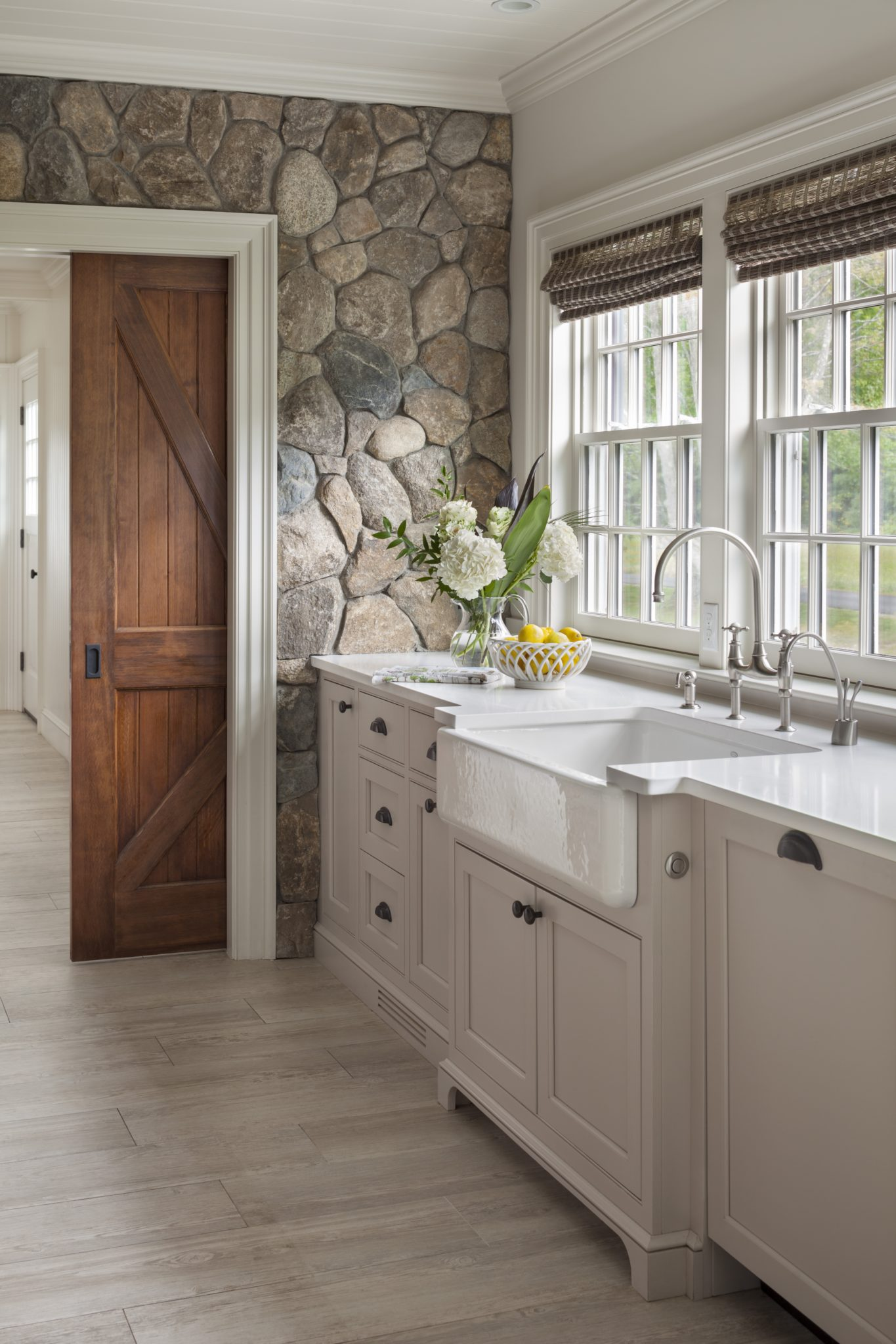 Farmhouse Kitchen with New England Fieldstone Accent Wall and Sliding Barn Door by Patrick Ahearn Architect