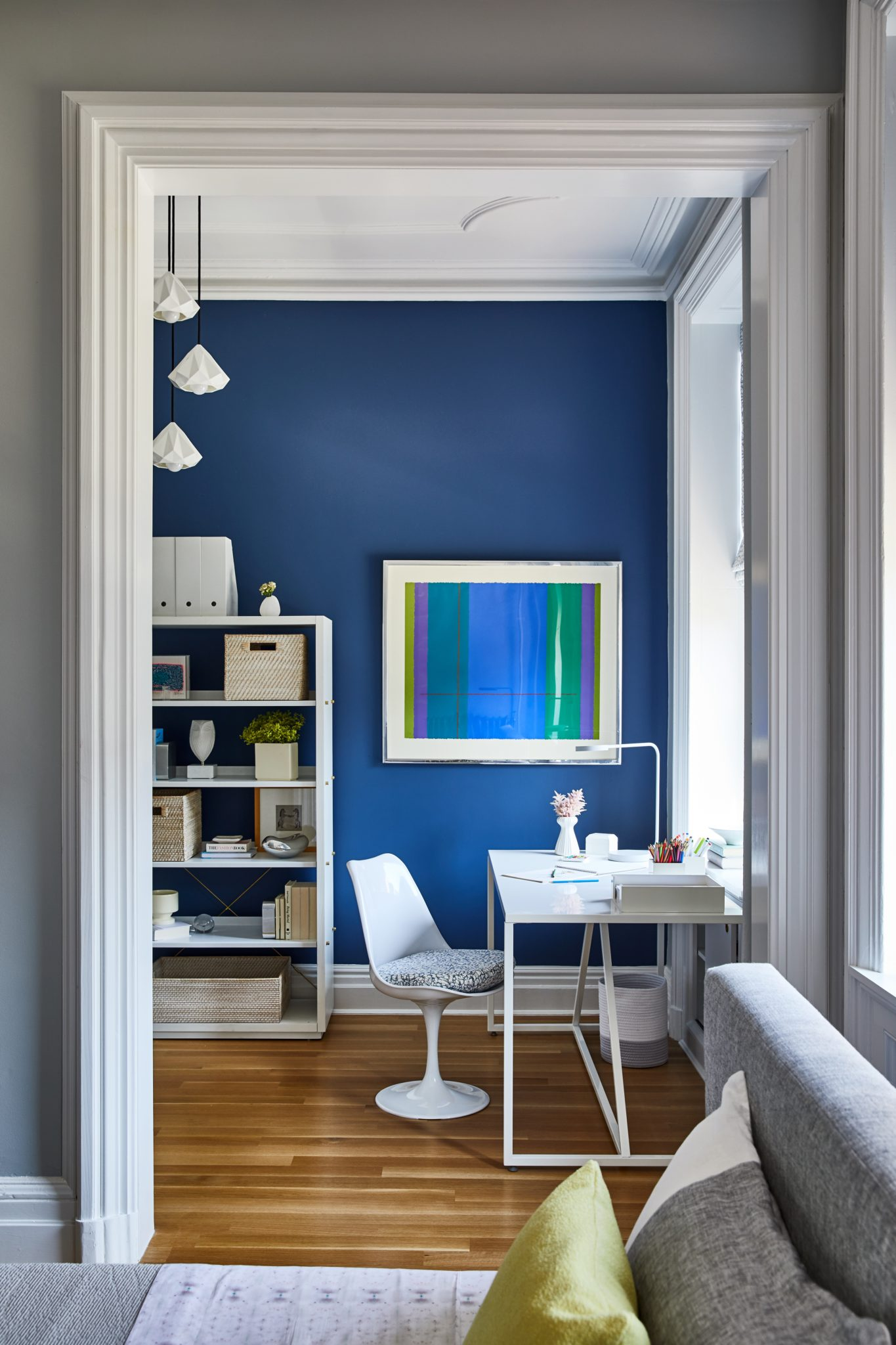Enger also created a clever workspace within a small alcove of the child's bedroom. Kensington Blue paint fromBenjamin Mooredecorates the accent wall. A lacquered Hayneedle chair with Rebecca Atwood fabric on the seat is set in front of a Blue Dot desk. The orb-style chandelier is from Horne, and the vintage artwork was sourced through J. PATRYCE DESIGN; the designer curates a collection of vintage goodsthat her clients can choose from for their projects.