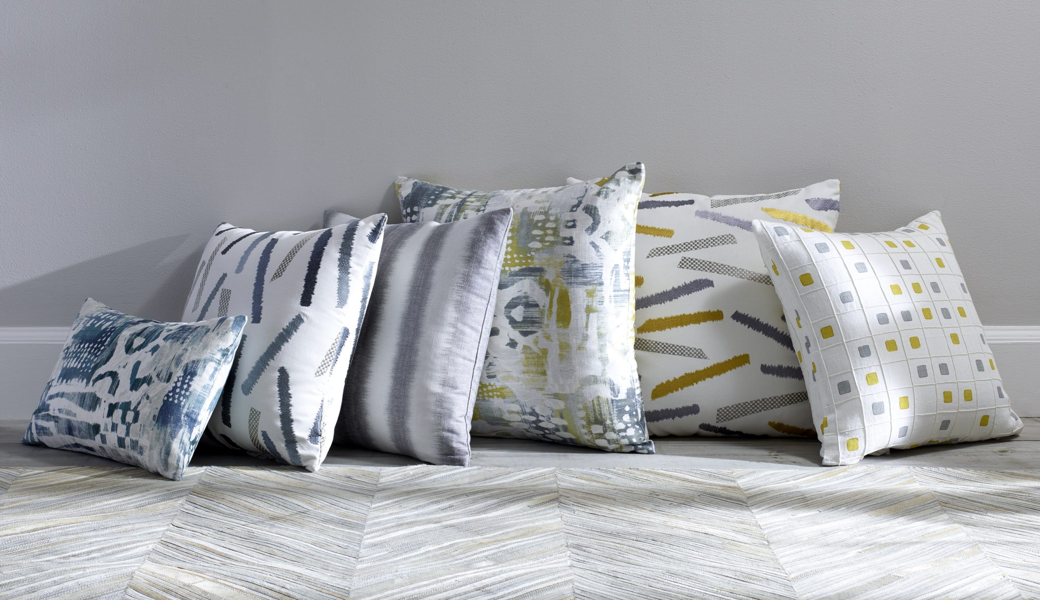 Shown here is a variety of pillows covered in the new Jeffrey Alan Marks fabrics. From left to right: Surfwood in Ocean; Tramonto in Ocean; Windswell in Pewter; Surfwood in Citrine; Tramonto in Citrine; Gridwork in Citrine.