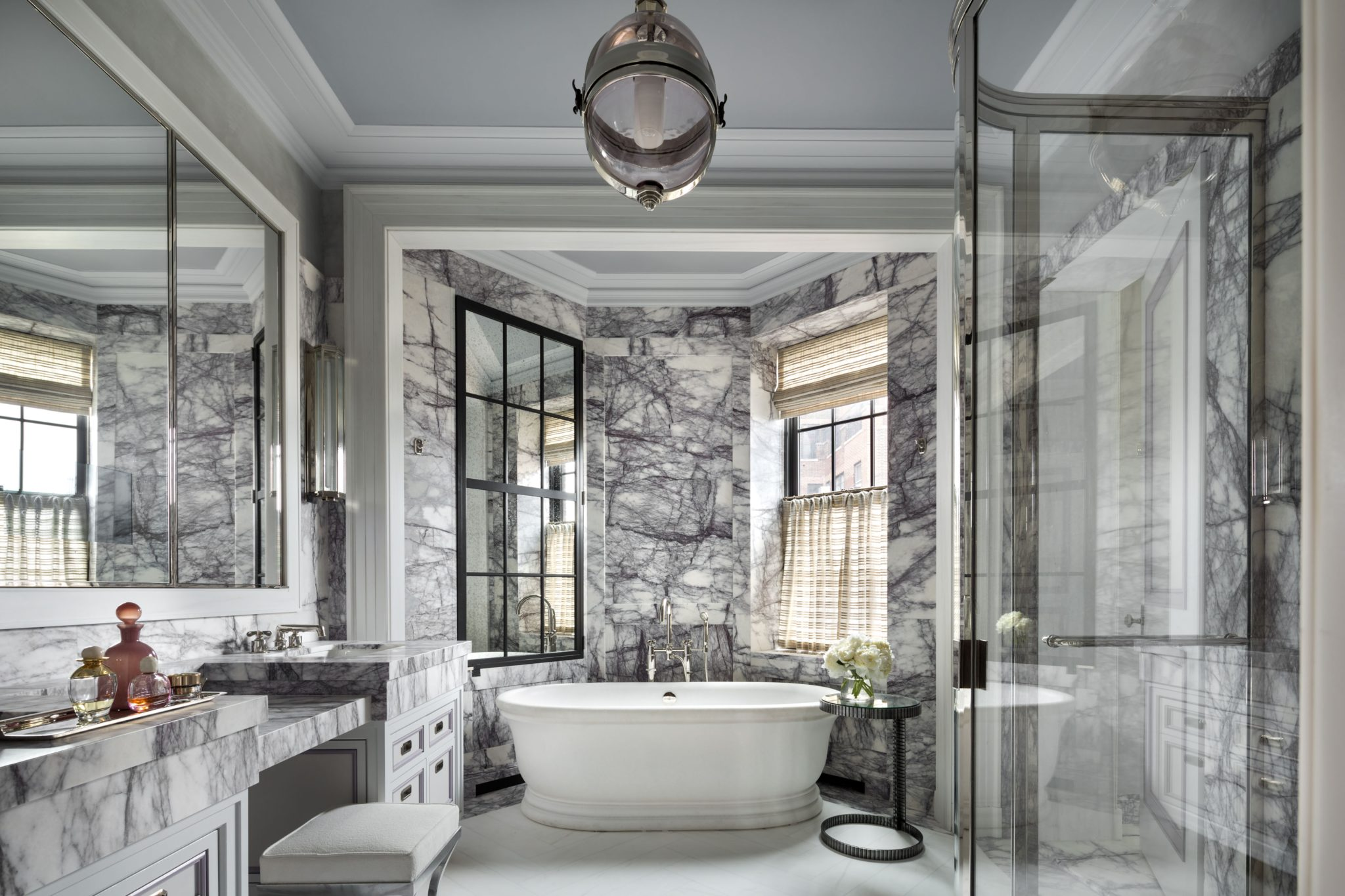 The master bath has stone floors and Lilac marble walls; a mirrored panel creates symmetry with an existing window. The tub is from Urban Archaeology with fittings by Waterworks; the pendant light is the Grayfoy by Steven Gambrel for Urban Electric Co.