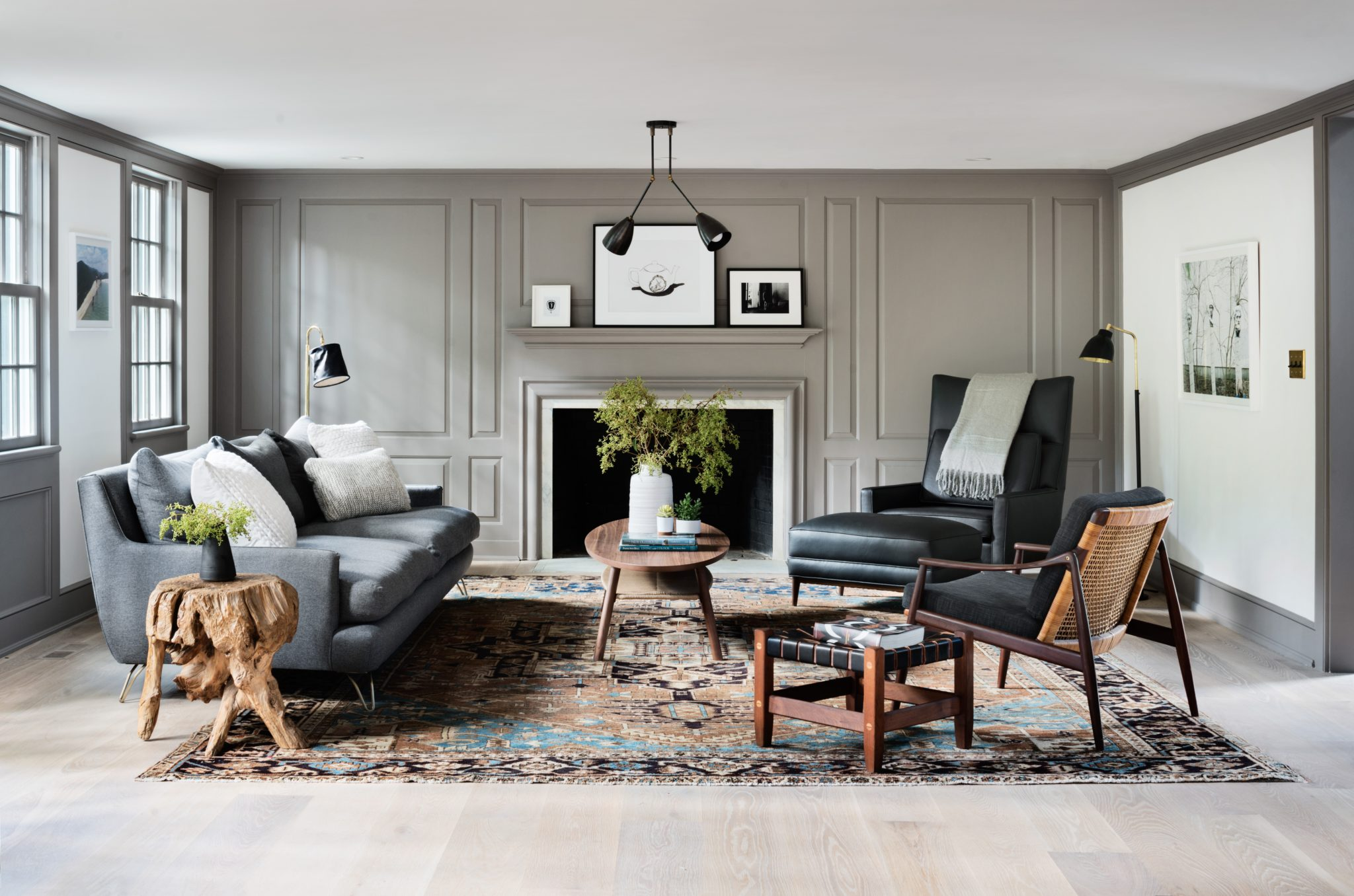 The living room's custom sofa by Montauk is upholstered in a Holland and Sherry fabric; the chairs and rug are vintage. New white oak flooring was installed throughout the house, and the walls, paneling, and trim in each room is painted in Farrow and Ball colors.