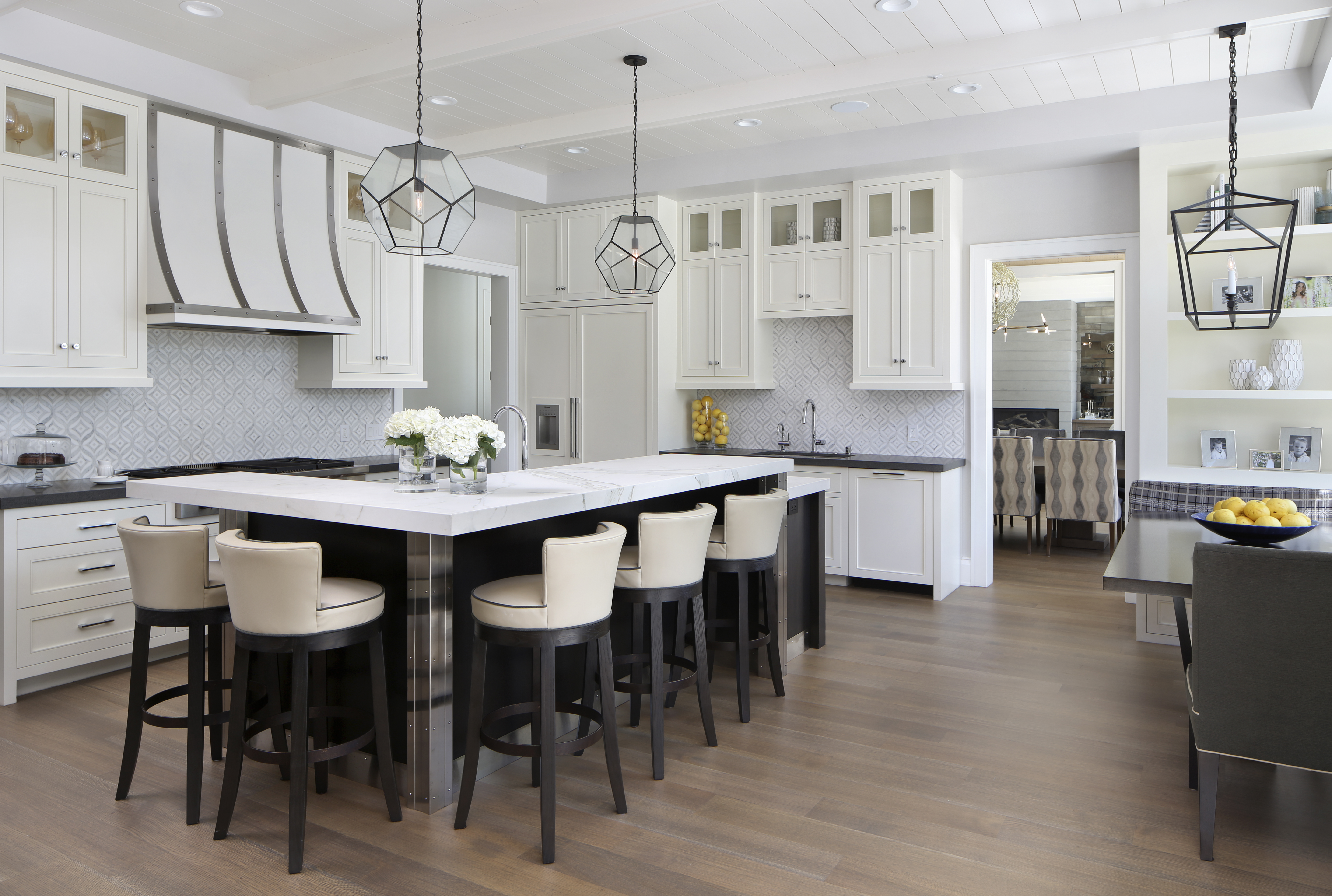 From the white-paneled ceiling to the bright cabinetry, this modern kitchen is full of light tones.The gray and white patterned backsplash, from Walker Zanger, matches the room's silver accents — from the hardware to the custom hood. The sleek countertop, made of Ann Sacks porcelain slabs, is accompanied with Lee Industries stools upholstered in Maharam fabric.