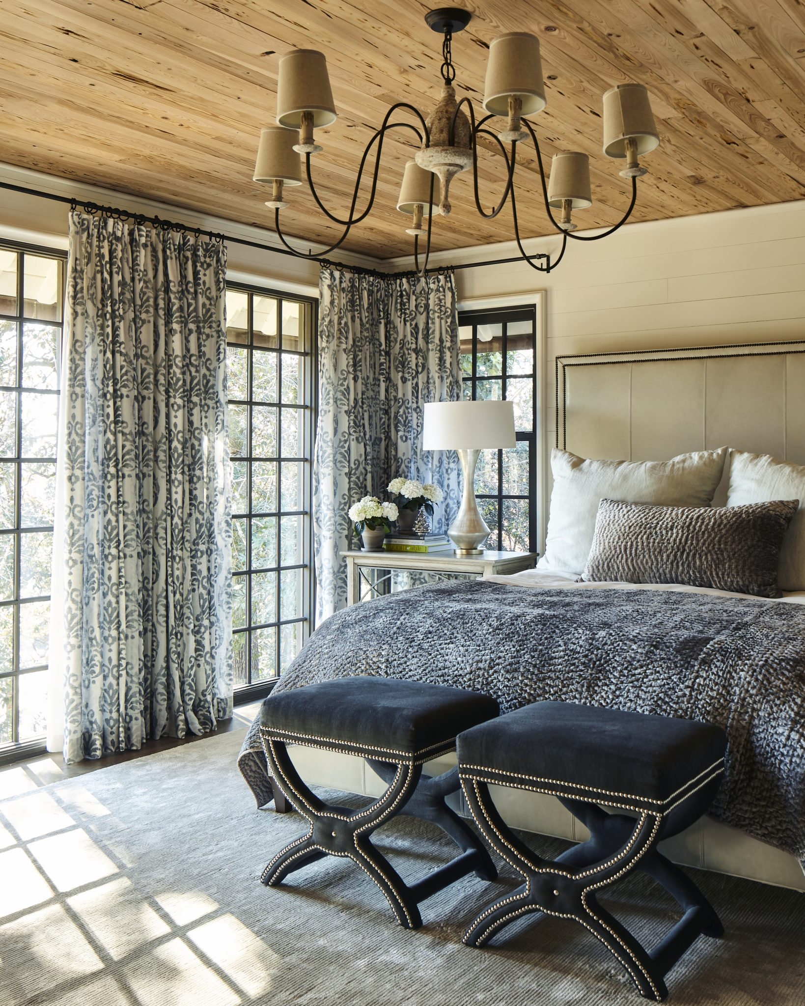 In this cozy, polishedbedroom, the cypress-paneled ceiling offers a dose of warmth to the blue-gray color palette and mixed patterns. The custom drapery was fabricated by Housewarmings in Birmingham, Alabama, and featuresfabric by Osborne & Little. The chic bed frame is by Lee Industries, sourced from Circa Interiors & Antiques in Birmingham; the bed linens are from Three Sheets;and the studded stools are from Arteriors.