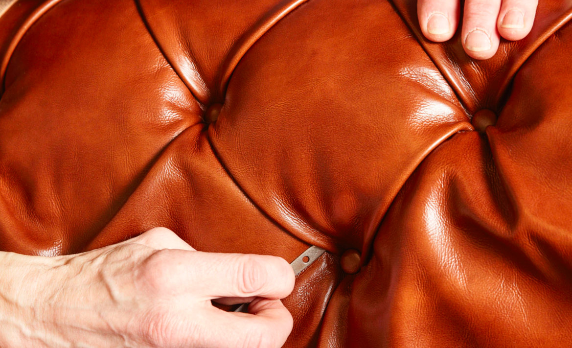 Upholsterers at Work  To protect the fillings and ensure correct placement, craftspeople wrap the springs in burlap and hand-tie them a second time. The grooves arefilled with natural horse hair, bringing voluptuous depth to the deep buttoned seat and back area. The artisans fit acotton lining around the horse hair to provide ease and minimize displacement.  Wielding40-centimeter upholstery needles, artisans upholster tufted diamonds through the fabric by hand; each diamond tuft relies onbuttons that are hand-crafted from the same fabric or leather. Upholsterers will use about 200 buttons for every Chesterfield sofa.