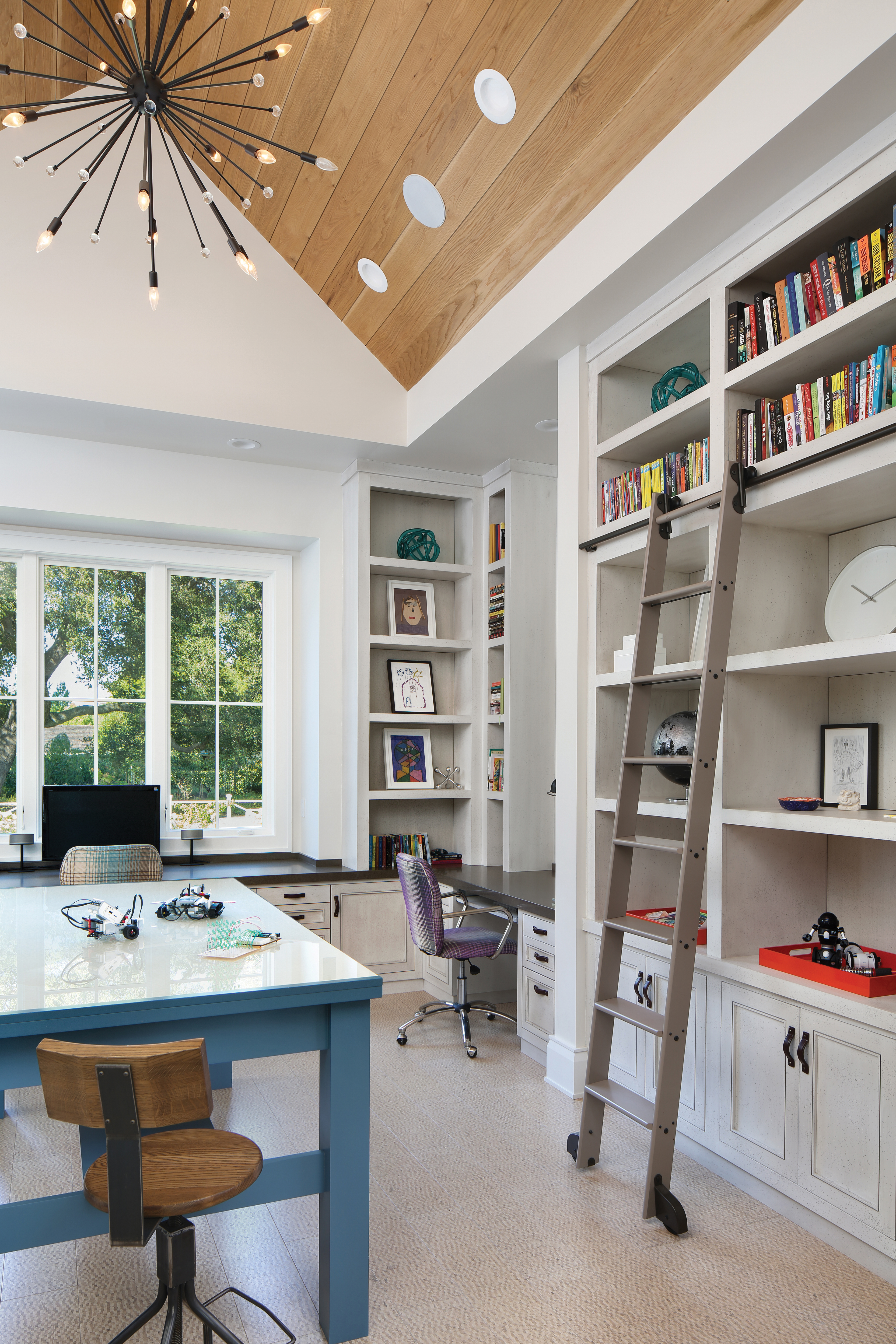 """Known as the project and study room, this unique space provides plenty of space for work and play. There is a 3Form glass top island and Caesarstone top desks, as well as pottery barn desk chairs with Osborn & Little fabric. """"This family,creative and playful at heart, can work on projects or puzzles on the large indestructible glass laminated island that was designed with science projects in mind,"""" Sullivan says. Built-in shelving, a wood vaulted ceiling, and cork flooring gives this space a creative touch."""