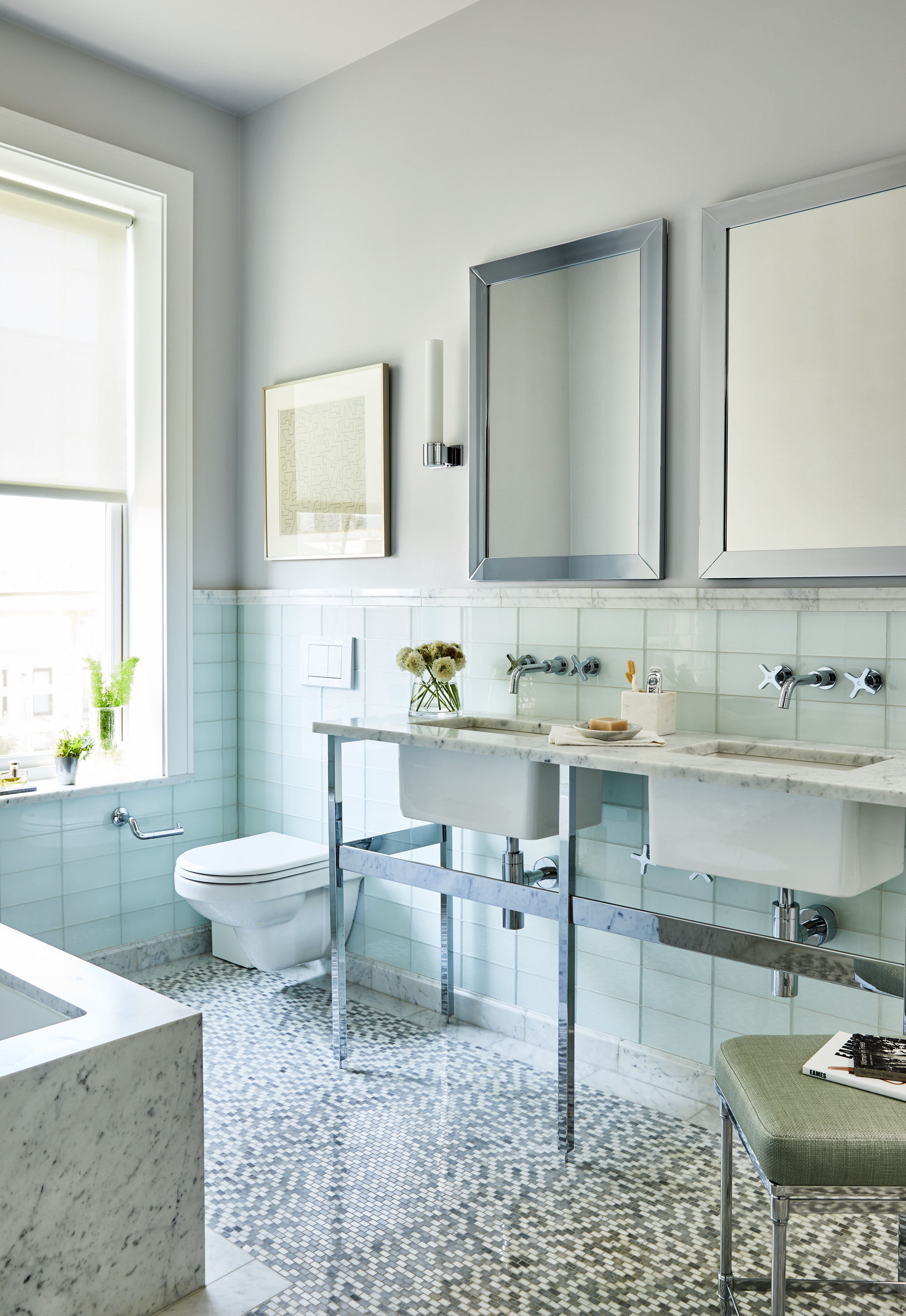 The master bath features a mix of serene, glossy textures and subtle colors, as well as elegant furnishings. The designer was inspired to choose a double open-legged washstand after she was inspired by a boutique hotel in Florence. Mosaic floor tile from Waterworks injects a dose of personality into the room.Elegant medicine cabinets from Restoration Hardwareare flanked by Waterworks wall sconces; the fixtures and toilet are byLefroy Brooks.