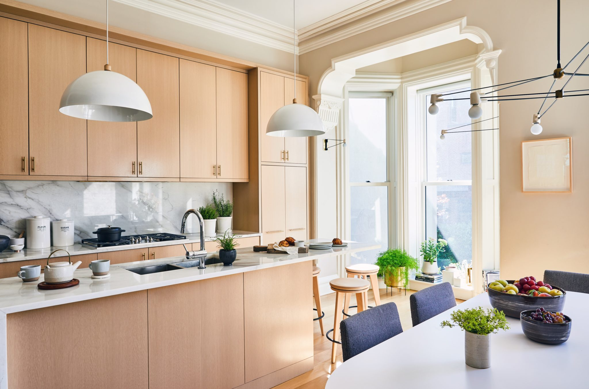 In the kitchen, the cerused rift white oak cabinetry was custom created by NR Wood Design in Brooklyn. Bright calacatta marble countertops from Langley Stone and Marble further lighten the look of the wood cabinetry. The sleek island pendant lights are from Allied Maker, and the bleached walnutstools are from Dennis Miller.