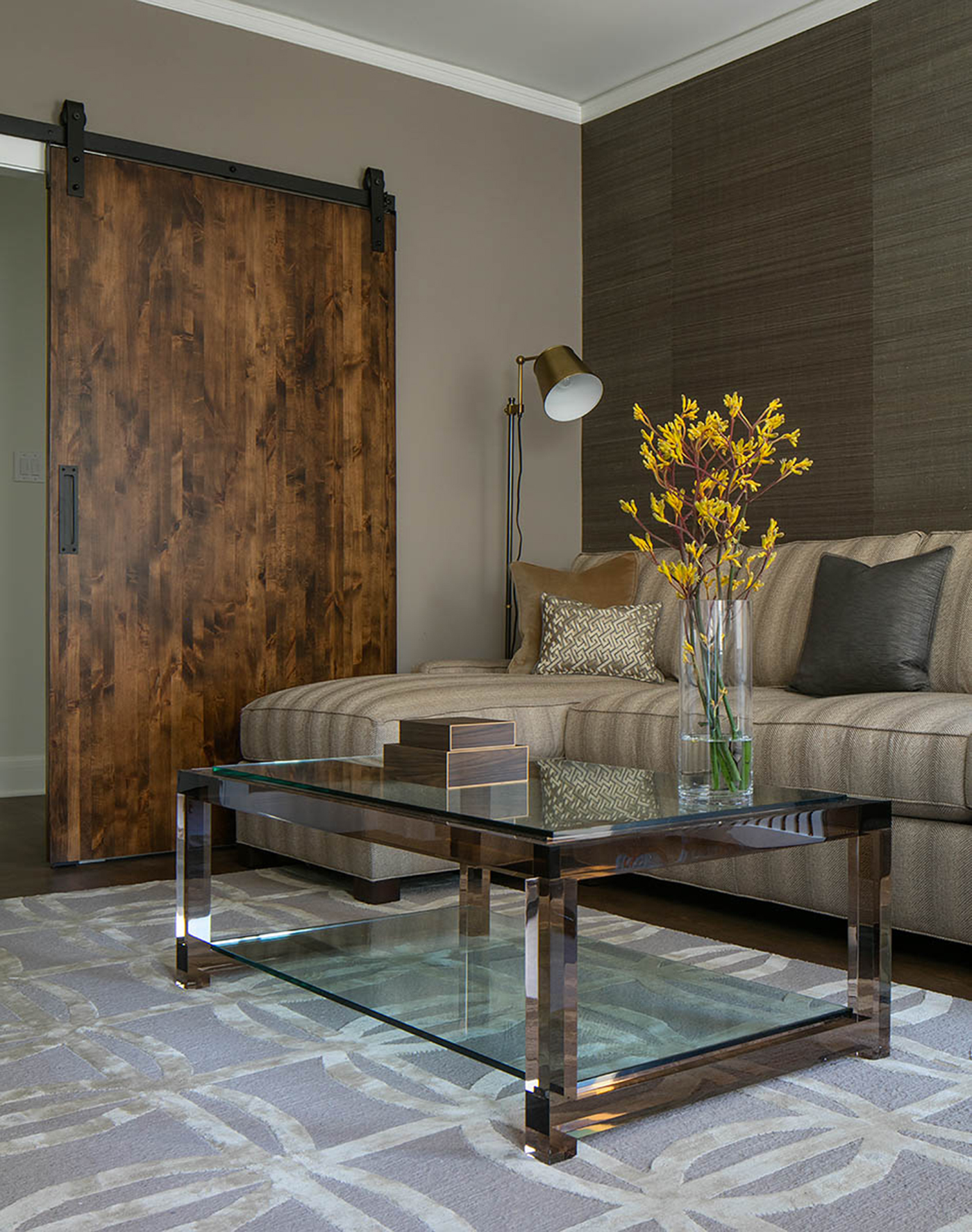 Sitting room with a refined take on a barn door and lucite coffee table by bd home