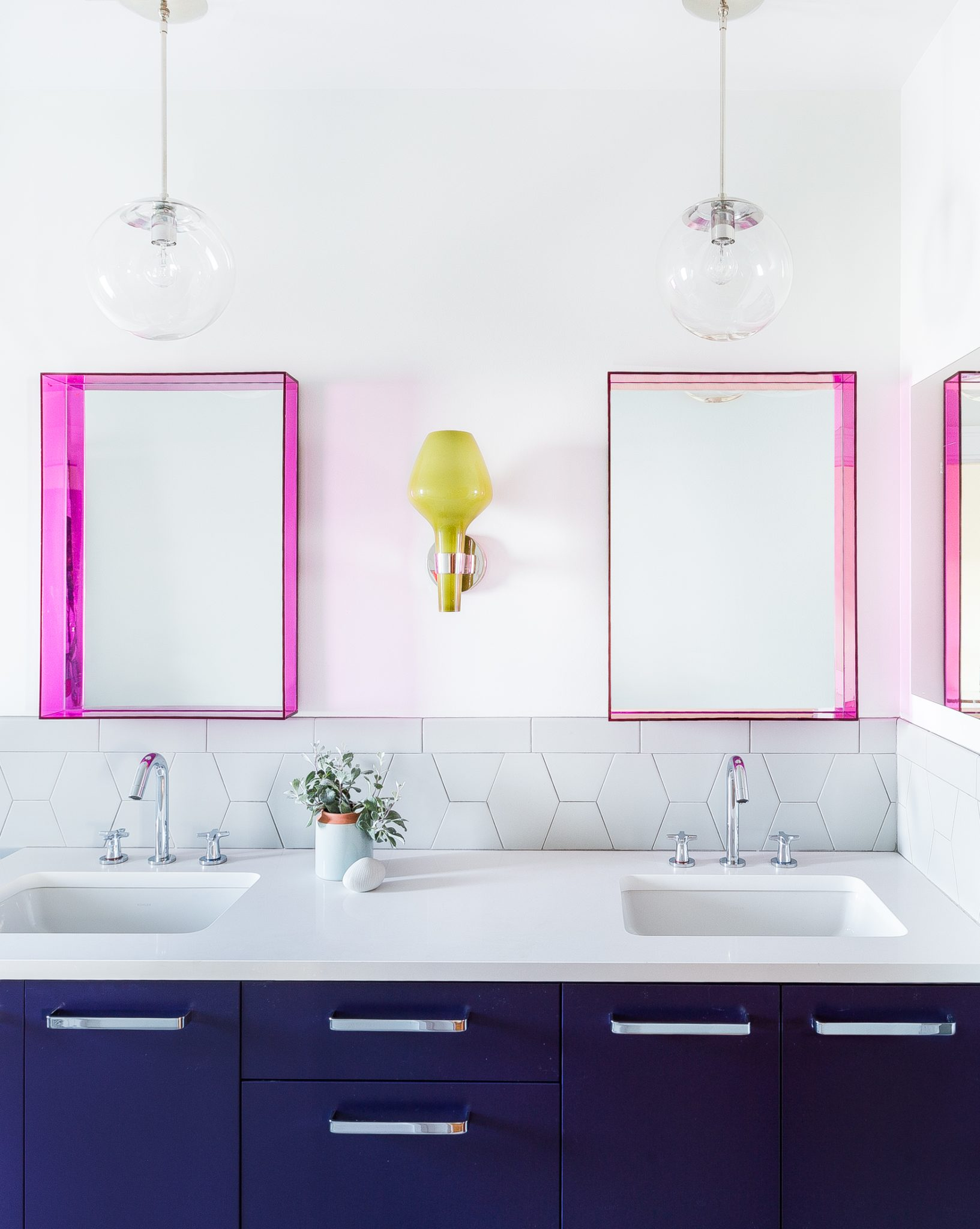 For the children's bath, Kenna approached the space with a distinctly contemporary style. A transparent acrylic finish gives the Kartell mirrors a fluorescent pink glow, which stands out against the white backsplash from Daltile. The pendant lights above the mirrors are from Schoolhouse.