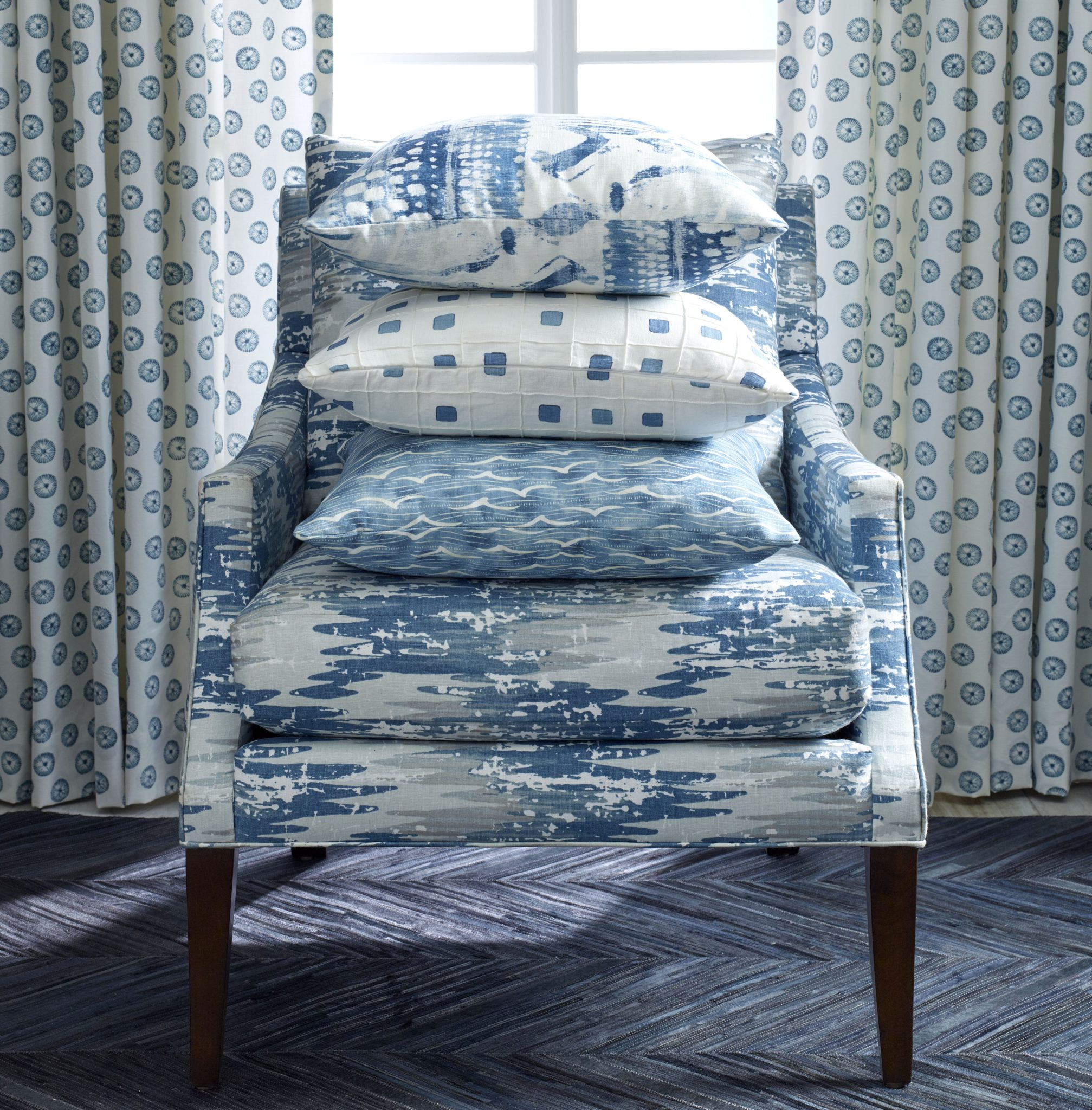 More of the new fabrics in ocean colors on display. The curtains are Onshore in Ocean; the chair is in Whitecap in River. The pillows, from top to bottom, are Surfwood in Ocean, Gridwork in Ocean, and Angelus in Pacific.