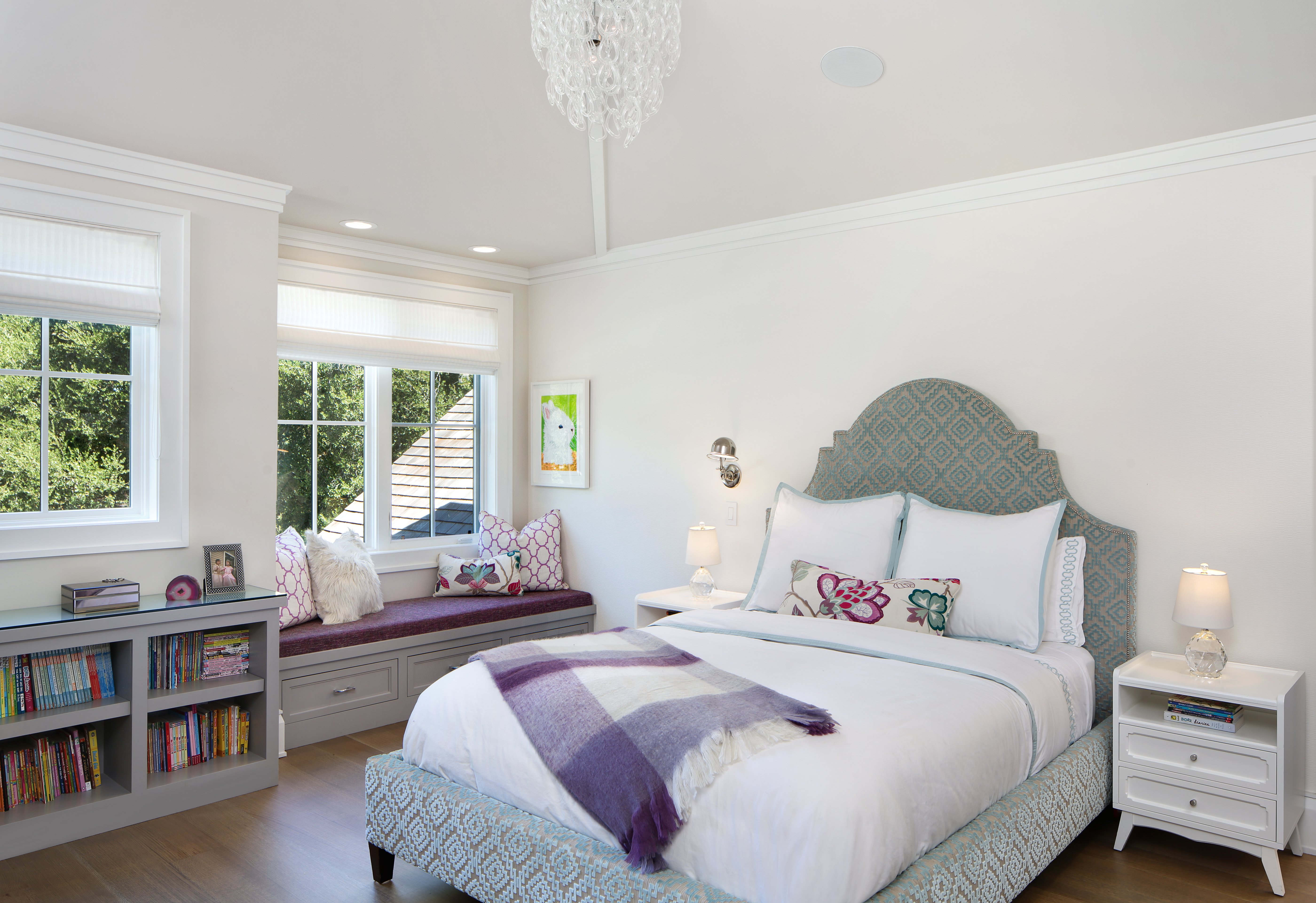 To create a space that is loved by both children and adults, the team pairs gray cabinetry and bright walls with light blue and purple accents. The bright Cowtan & Tout wallcovering adds subtle texture to the girl's bedroom, while the crystal light fixtures add a touch of elegance. The bed is from Bernhardt Lindsey and is upholstered with Harris Fabric. The duvet, sheets, and shams are from Serena & Lily and the nightstands are from The Land of Nod.