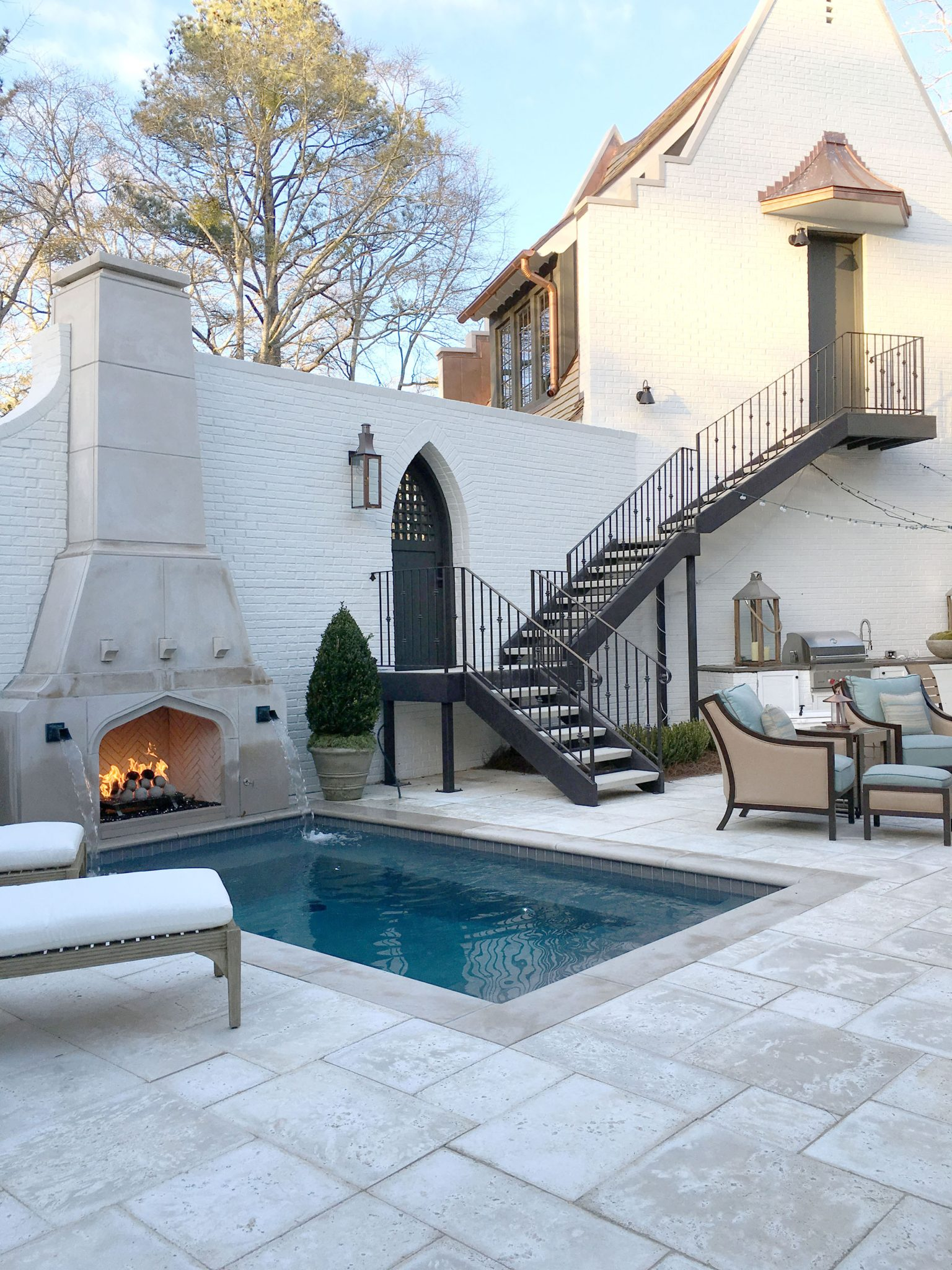 A beautiful courtyard features an outdoor kitchen, fireplace, and pool. The furnishings are from Summer Classics.