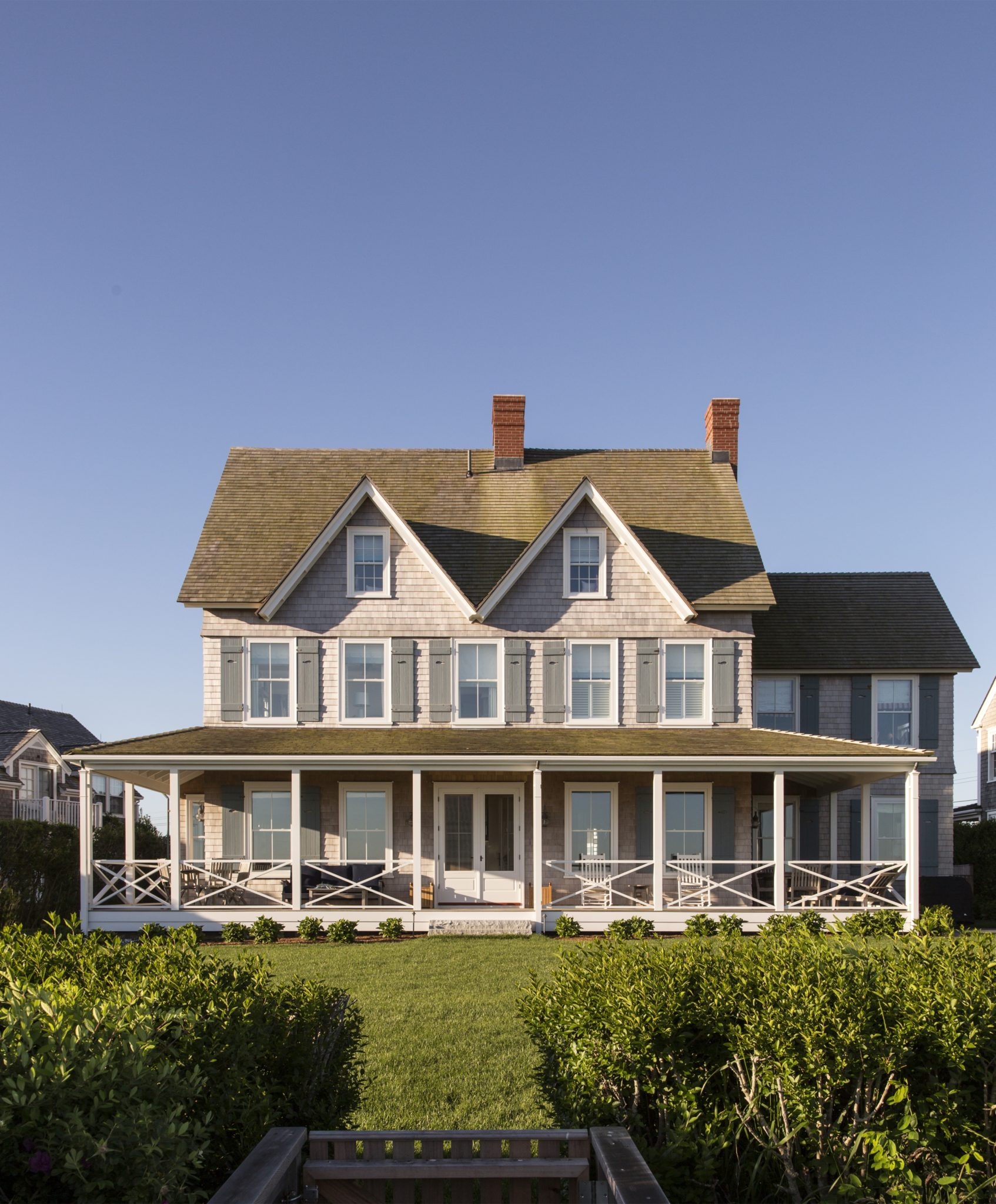 Beautiful shingle style beach house with wrap around porch by SLC Interiors