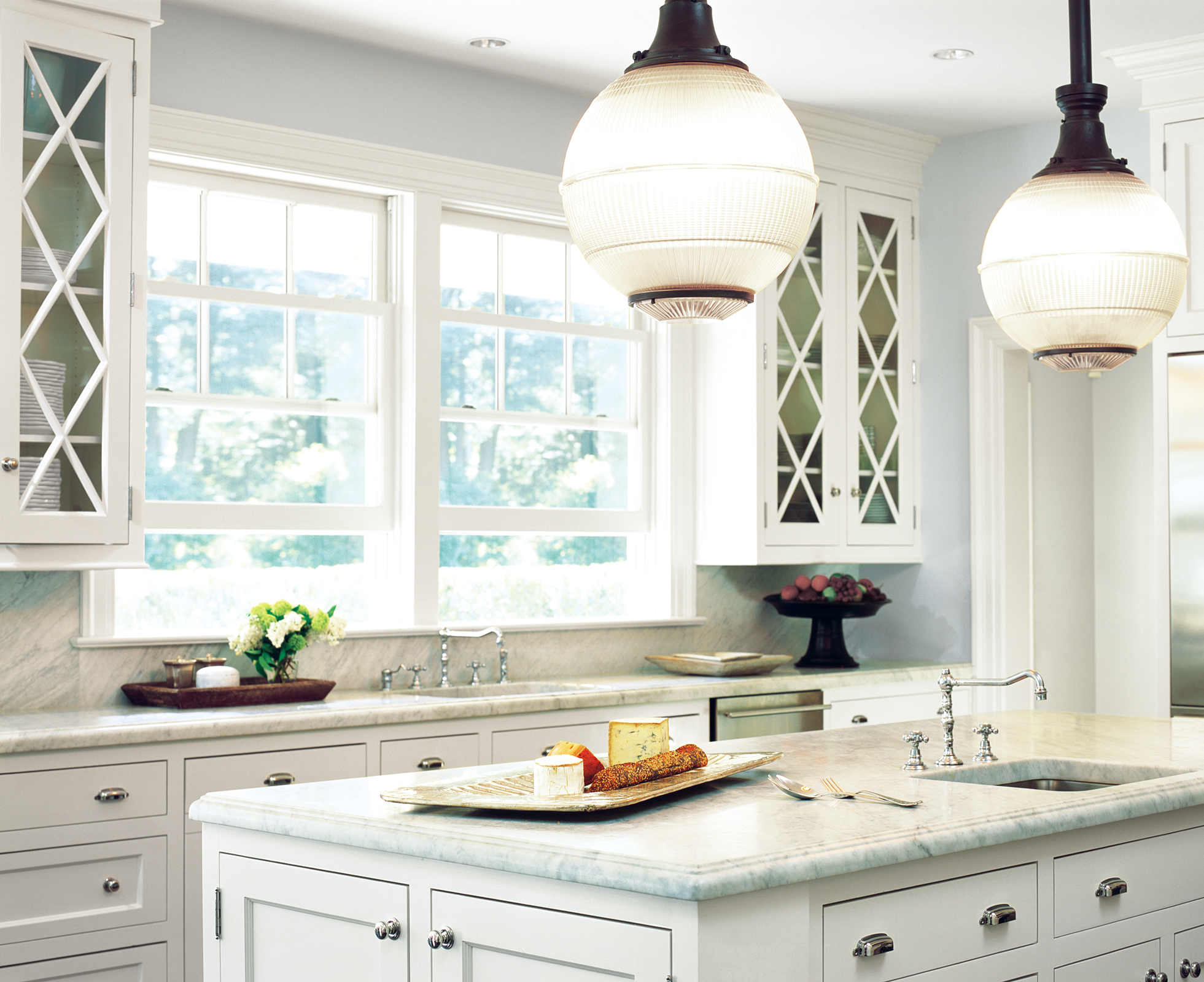 A white kitchen with marble backsplash and island by Linherr Hollingsworth