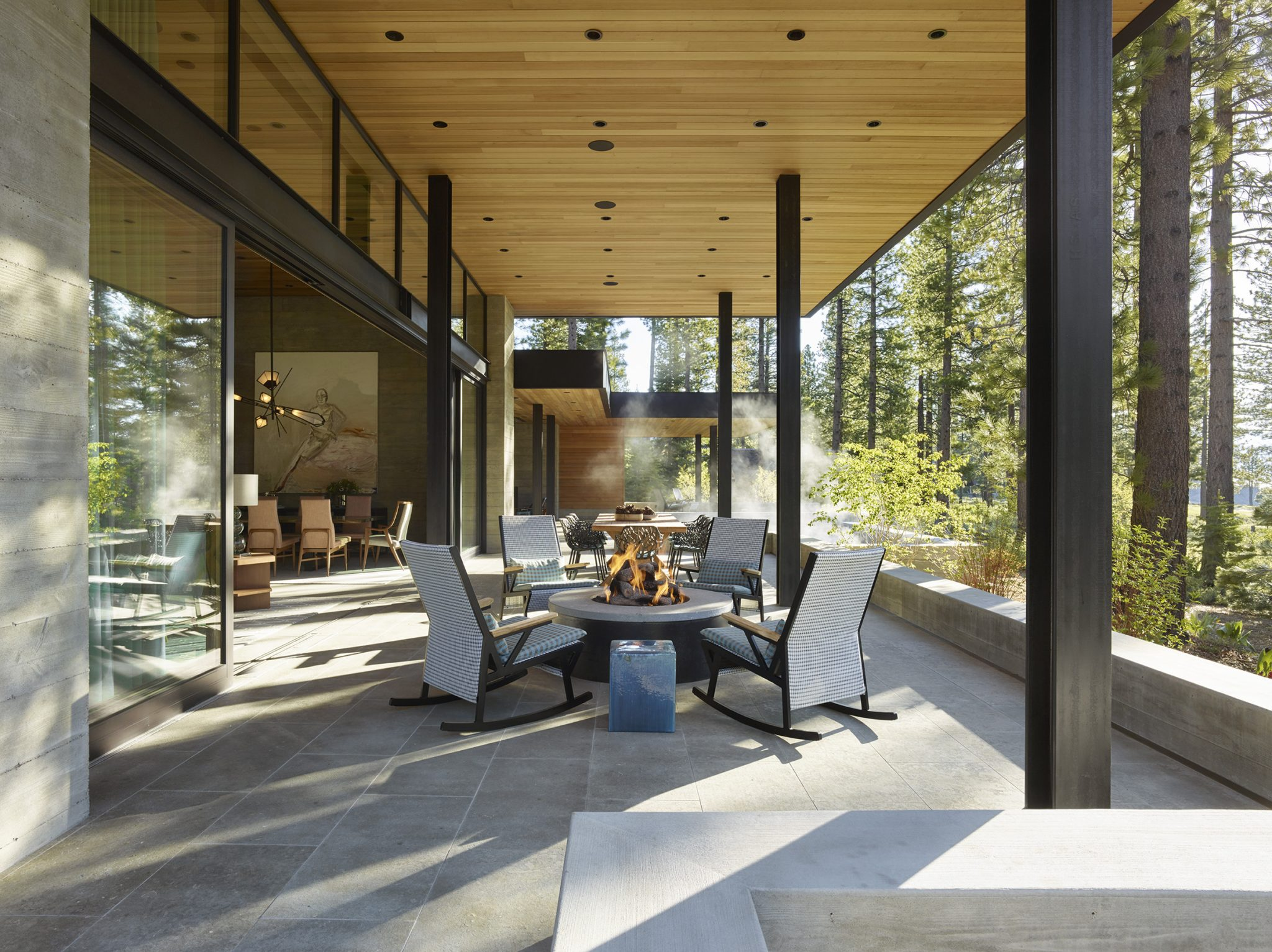Rocking chairs by Kettal surround the firepit; the dining table in the background is by Teak Warehouse, and the dining chairs are by Janus et Cie.