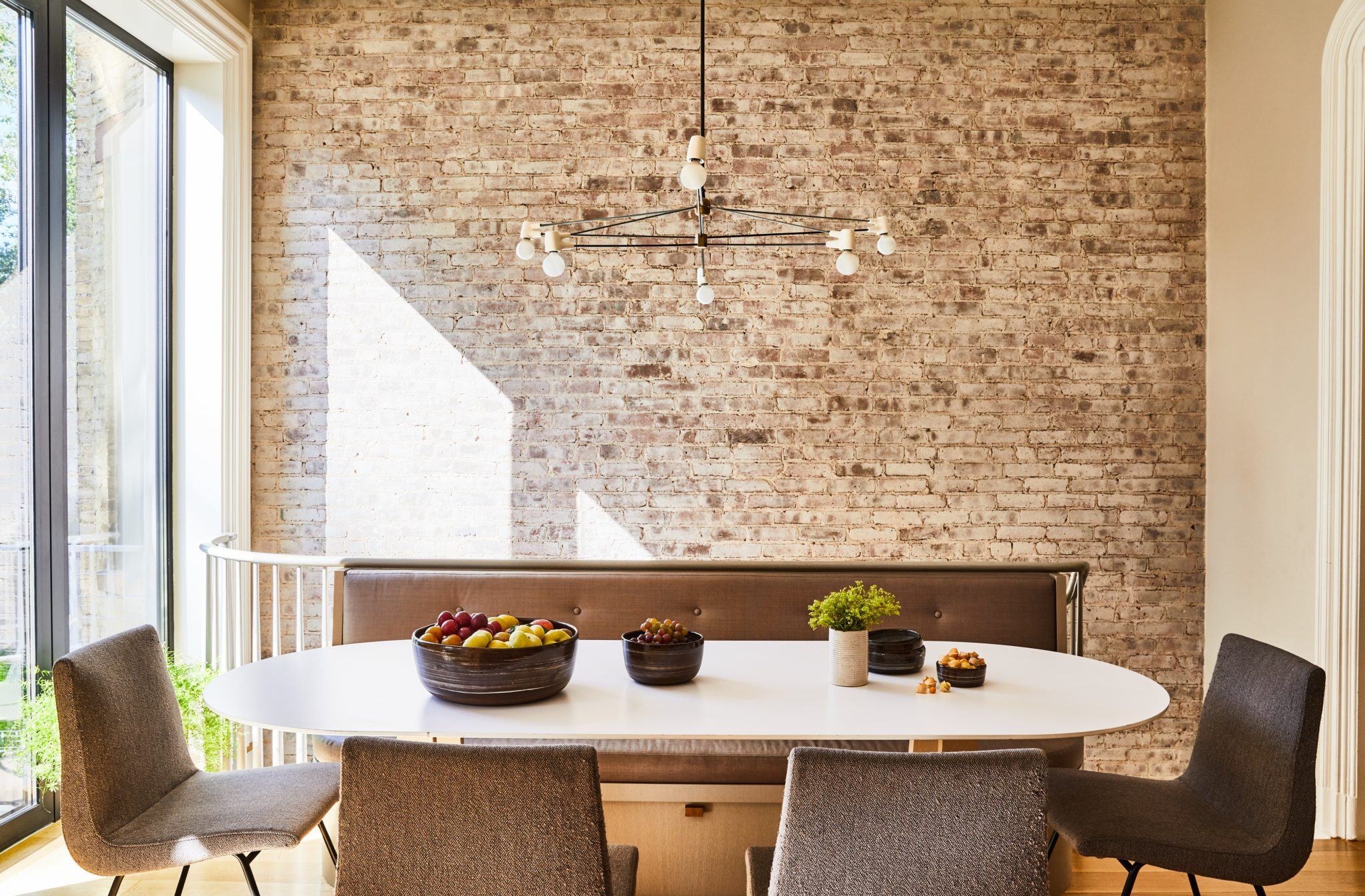 Just outside the kitchen area, a contemporary chandelier from Brendan Ravenhill Studio contrasts with the industrial brick wall, original to the house. NR Wood Design built the custom curved dining table and cozy banquette, the later of which Enger outfitted in silvery fabric from Holly Hunt. The textured dining chairs are from Ligne Roset.