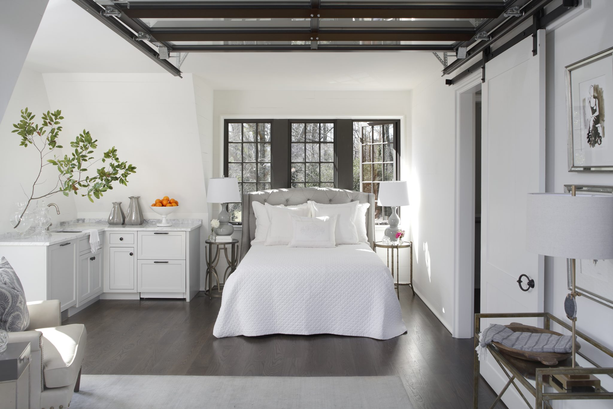 Overhead, the custom-designed steel garage door opens to allow increased space in the guest suite above the existing two-car garage. A tufted headboard from Birmingham Wholesale Furniture adds sophistication to the space; the table lamps and night stands are also from Birmingham Wholesale Furniture.