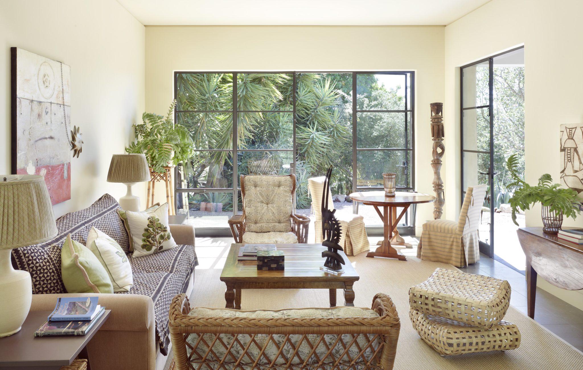 Bright living room with natural materials, doors onto garden by Suzanne Rheinstein & Associates