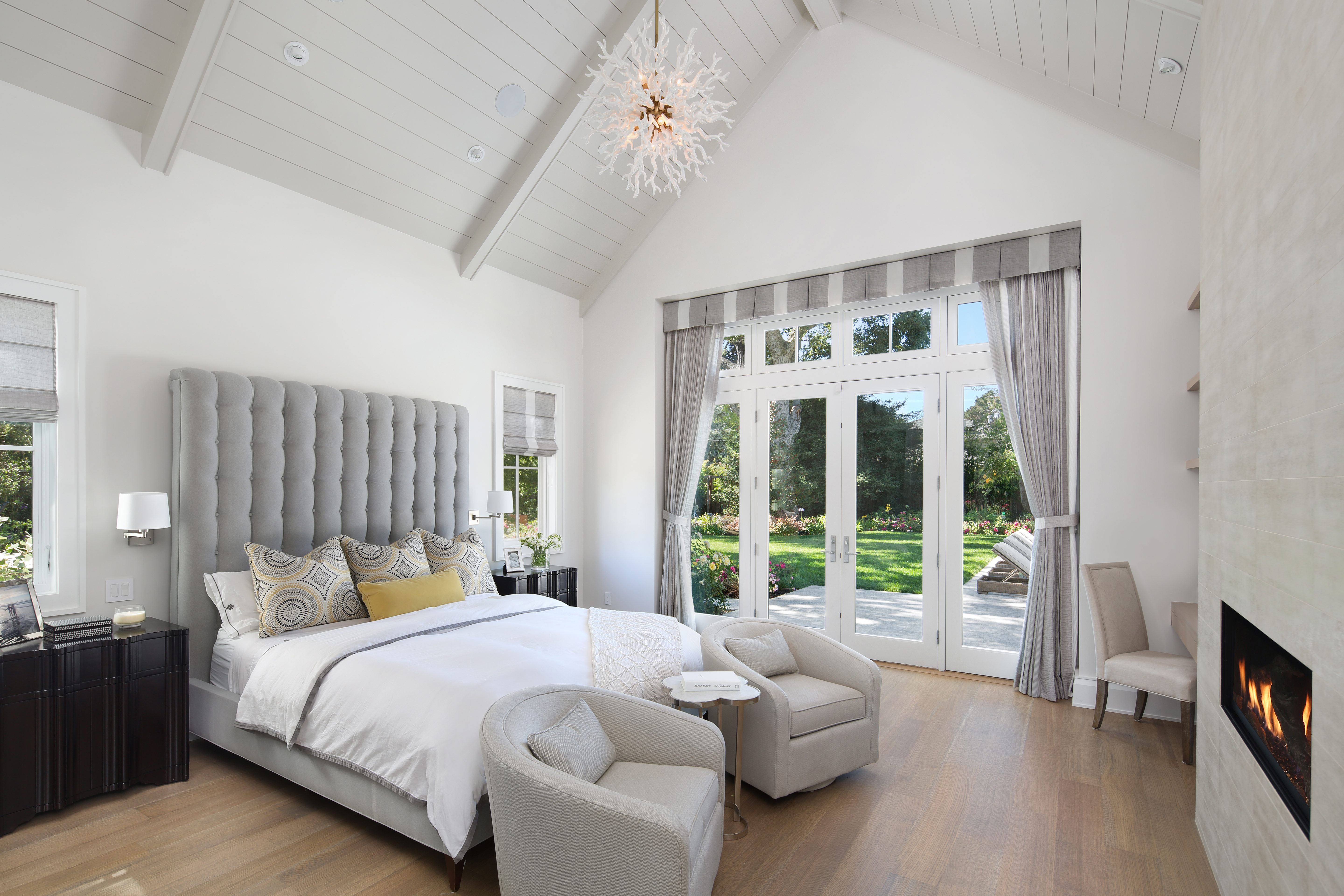 Enter this light-filled master bedroom from the patio. Crisp, white walls and a vaulted ceiling set the basis for this fresh, clean space.Completed with a gray, tufted headboard, the bed is from Hickory Chair. Nightstands from Oly Studio sit beside the bed, while swivel chairs from Room & Board sit at the foot of the bed.Acrossthe room,Daltile porcelain tiles make up the fireplace mantel.