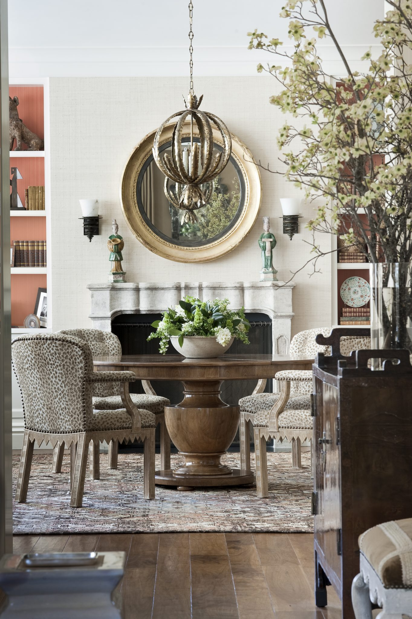 """""""Scale and proportion are key,"""" says Tucker.From the living room, the dining room is visible, and its design adds depth the rest of the space. The walnut pedestal dining table was custom designed by Tucker & Marks and fabricated by Rose Tarlow Melrose House. Tucker and her team upholstered chairs originally designed by Michael Taylor, which Tucker had safe-guarded in her personal collection, in fabric from Cowtan & Tout, and they added a braid trim from George Spencer Designs. The South Persian Bakhtiari carpet, circa 1900, underpins the design. Over the table, thebrutalist-style pendant light in an antiqued bronze finish was designed by Tom Greene for Feldman Lighting around 1970."""