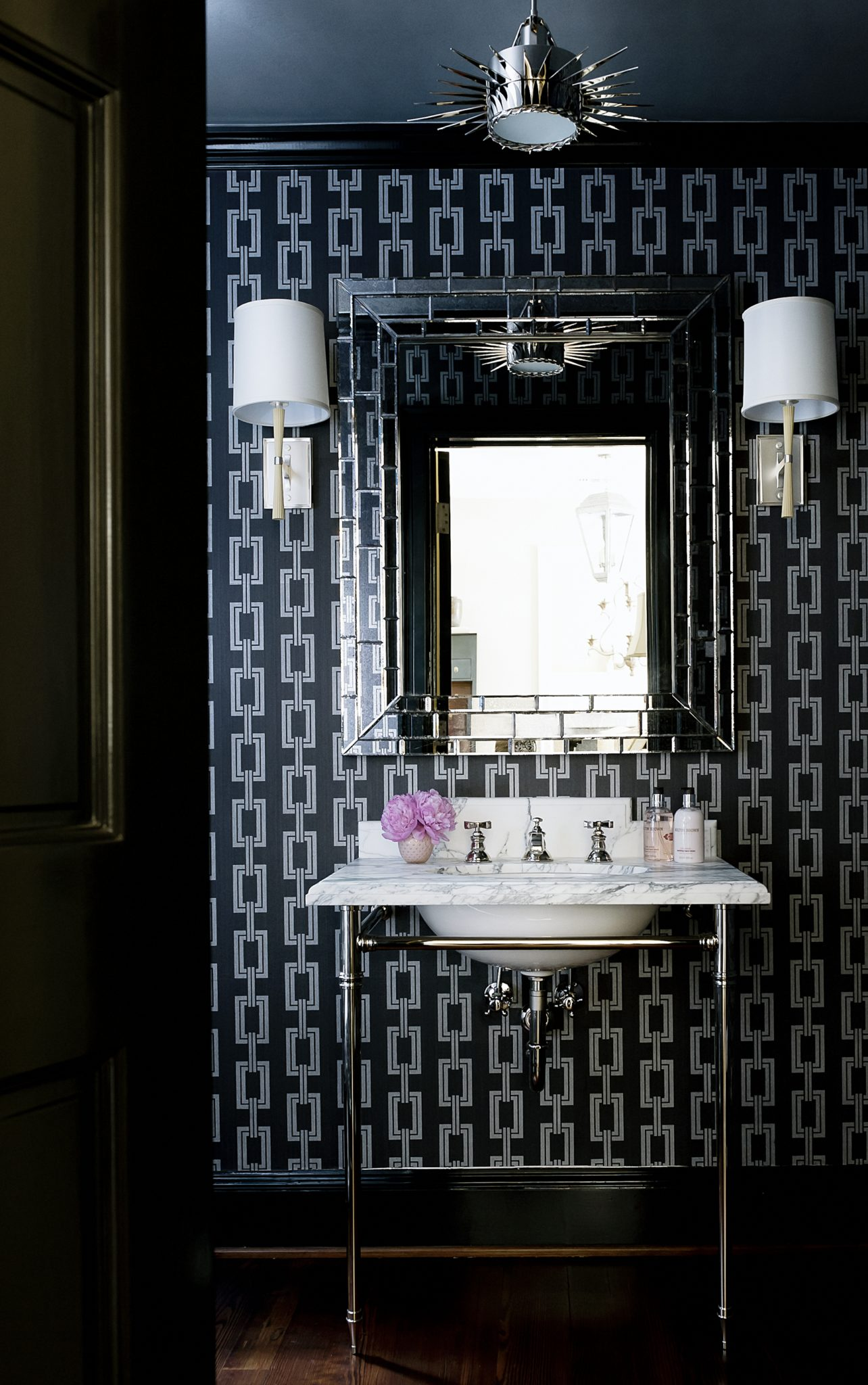 """""""We never want residents or guests to 'want' for anything."""" —Courtney Hill Interiors, Houston, TX  Favorite Finishing Touches: """"Fresh flowers, art, and accessories. In the bathroom, monogrammed linen hand towels, a pretty tray for guest towels, a bud vase, and luxurious hand wash and lotion.""""  Design Advice: """"Since this space [pictured above] is a powder room at the end of a hallway, we wanted the design to be impactful with all of the elements deliberate and well thought-out. The finishing touches are held in all of the juxtapositions throughout the space – the soft pink flowers and rose scented soap against the anthracite walls; the silk sconce shades against the rigid design of the wallpaper; and the feminine qualities of the accessories against the edginess of the angles in the room. We always strive to leave a space feeling functional, comfortable, and lived in. We never want residents or guests to 'want' for anything – in a bathroom, there should be good lighting, fragrances, soaps, hand towels, etc. Additionally, a lack of art and accessories are evidence of an incomplete space."""""""