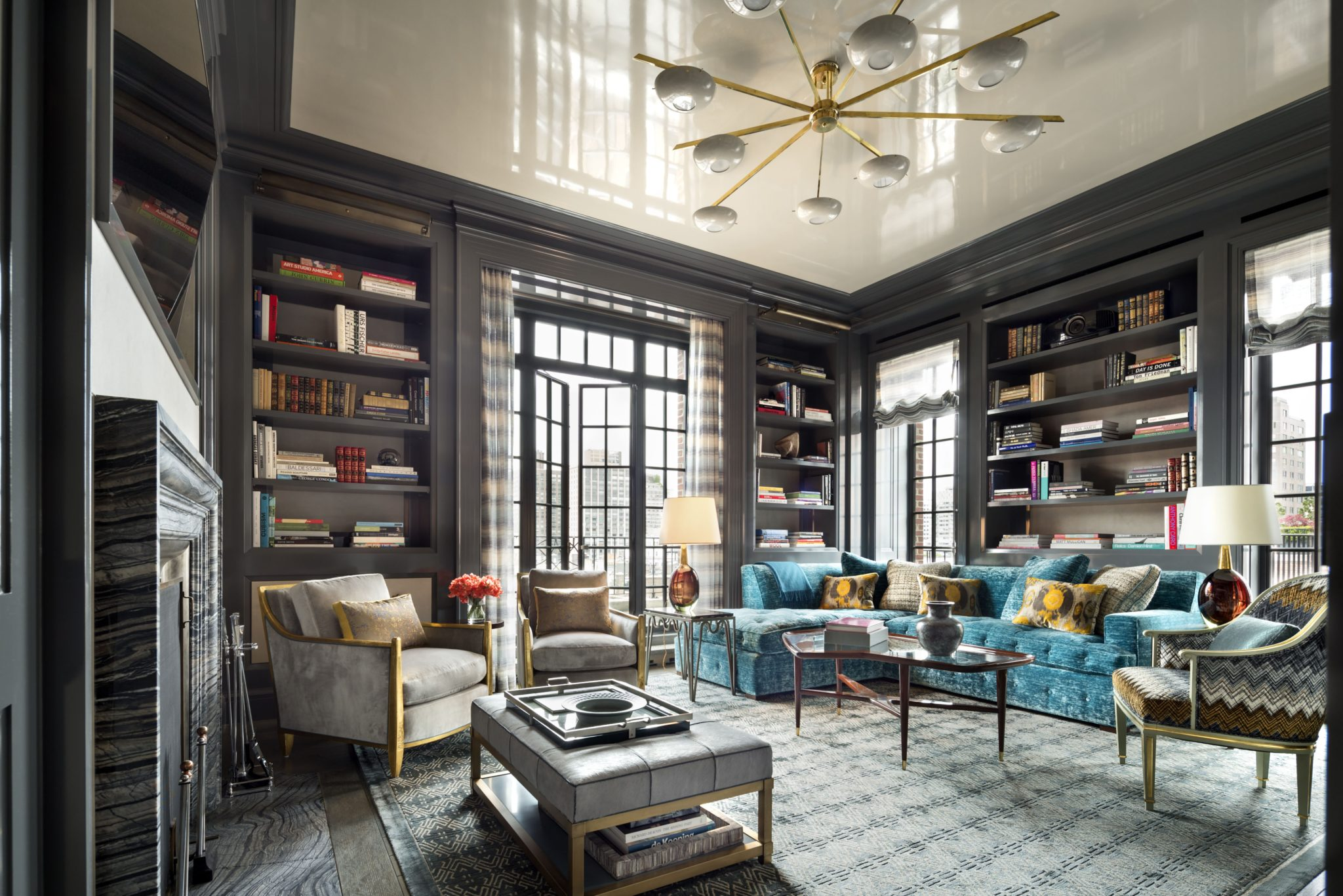 The paneled library opens to the terrace through new French doors. In the corner is a custom-made sectional sofa covered in Zoffany velvet; the Italian cocktail table is circa 1950.
