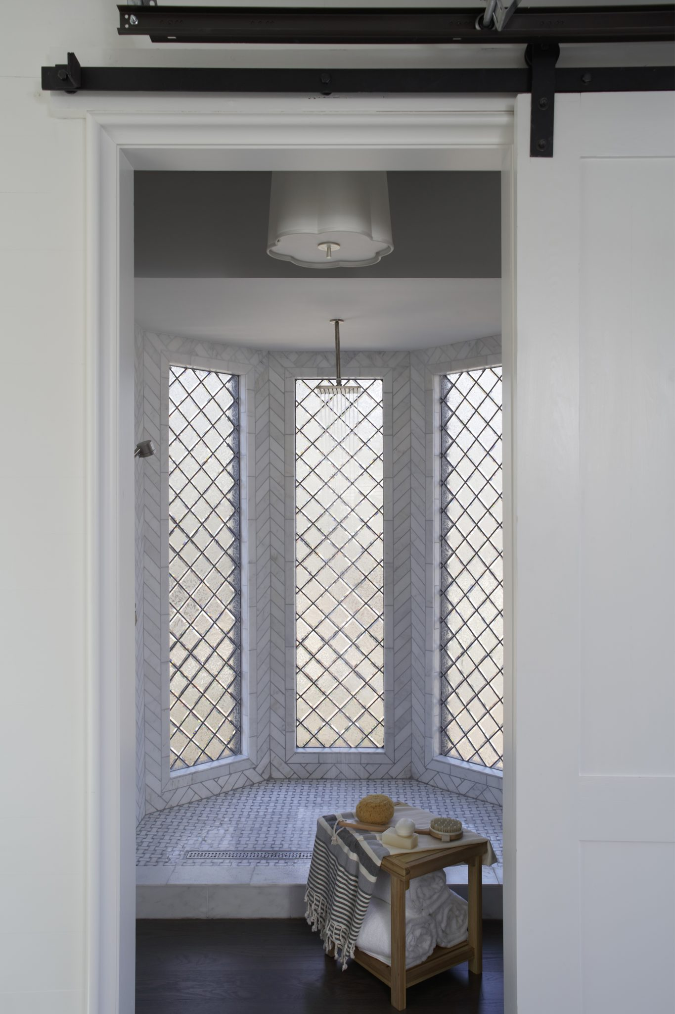 Within the walk-in marble shower, Christopher Architecture & Interiorsdesigned a custom lead-glass window to facilitate natural light and ornament the exterior.