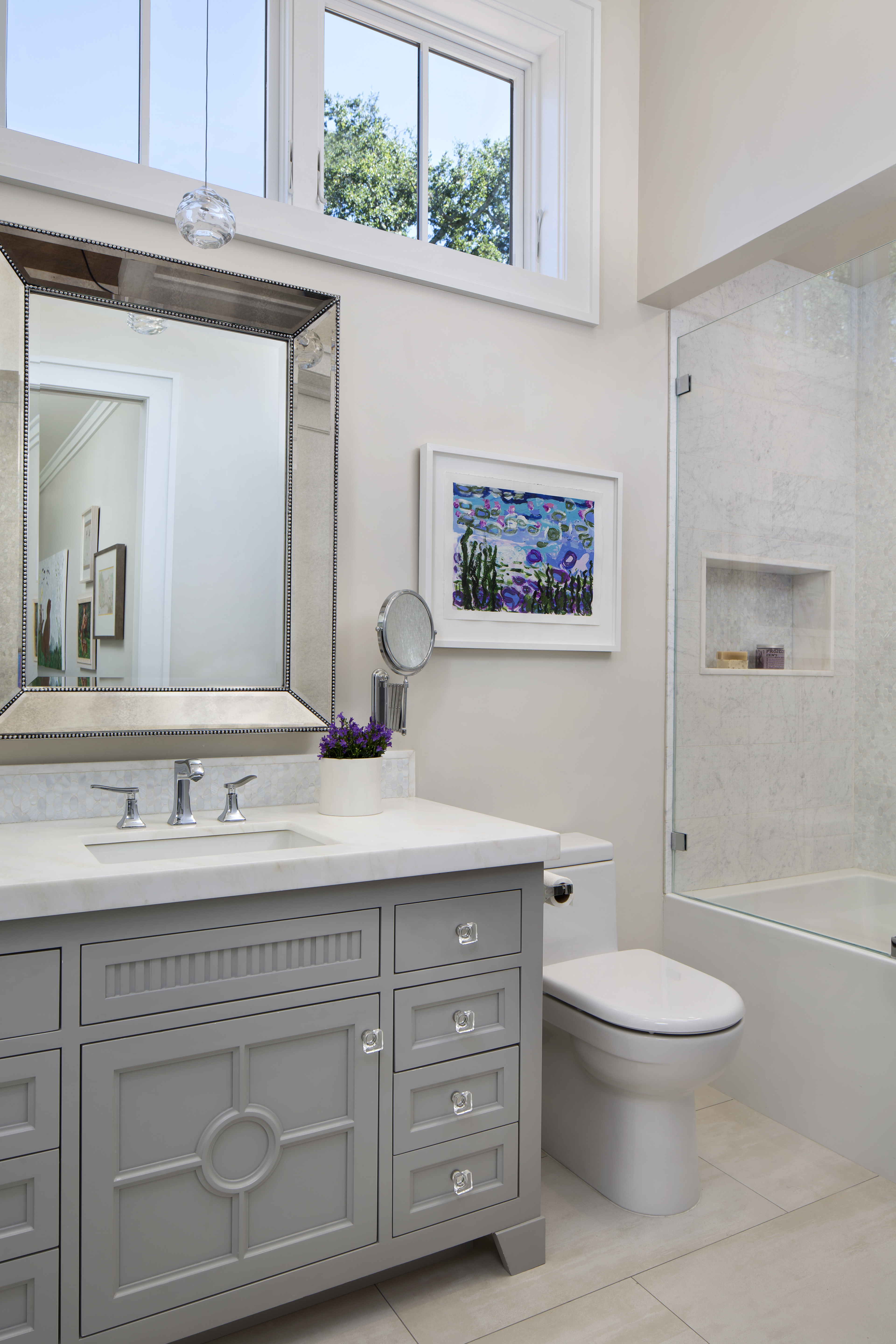 Enter the girl's bathroom, where Artistic Tile is used on both the floor and the shower wall. The spacereflects the decor of the adjoiningbedroom — fromthecrystal pendant andknobs tothe purple flowers and colorful painting.
