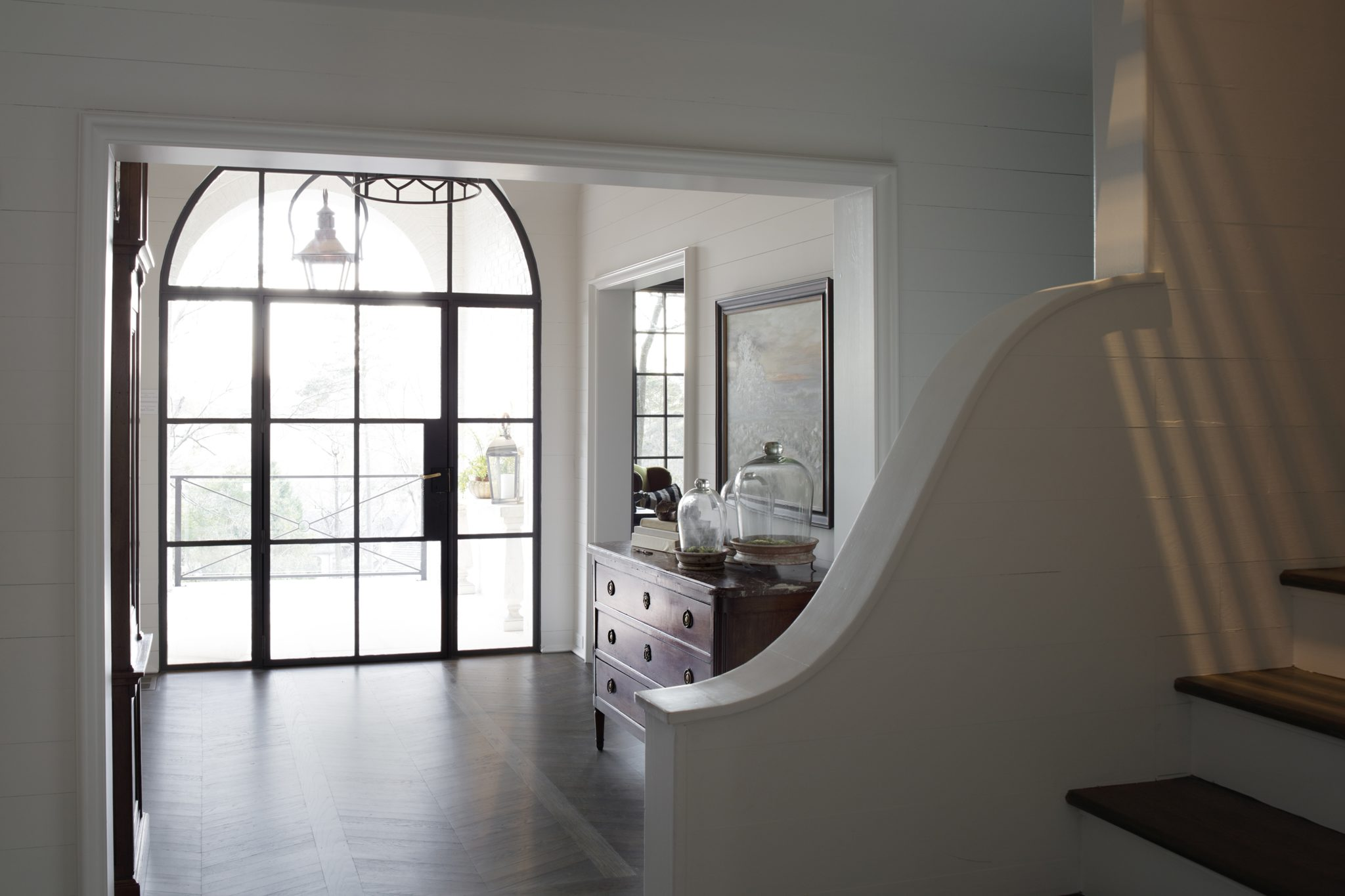An expansive, glassfront door creates a seamless transition from outdoors to indoors.