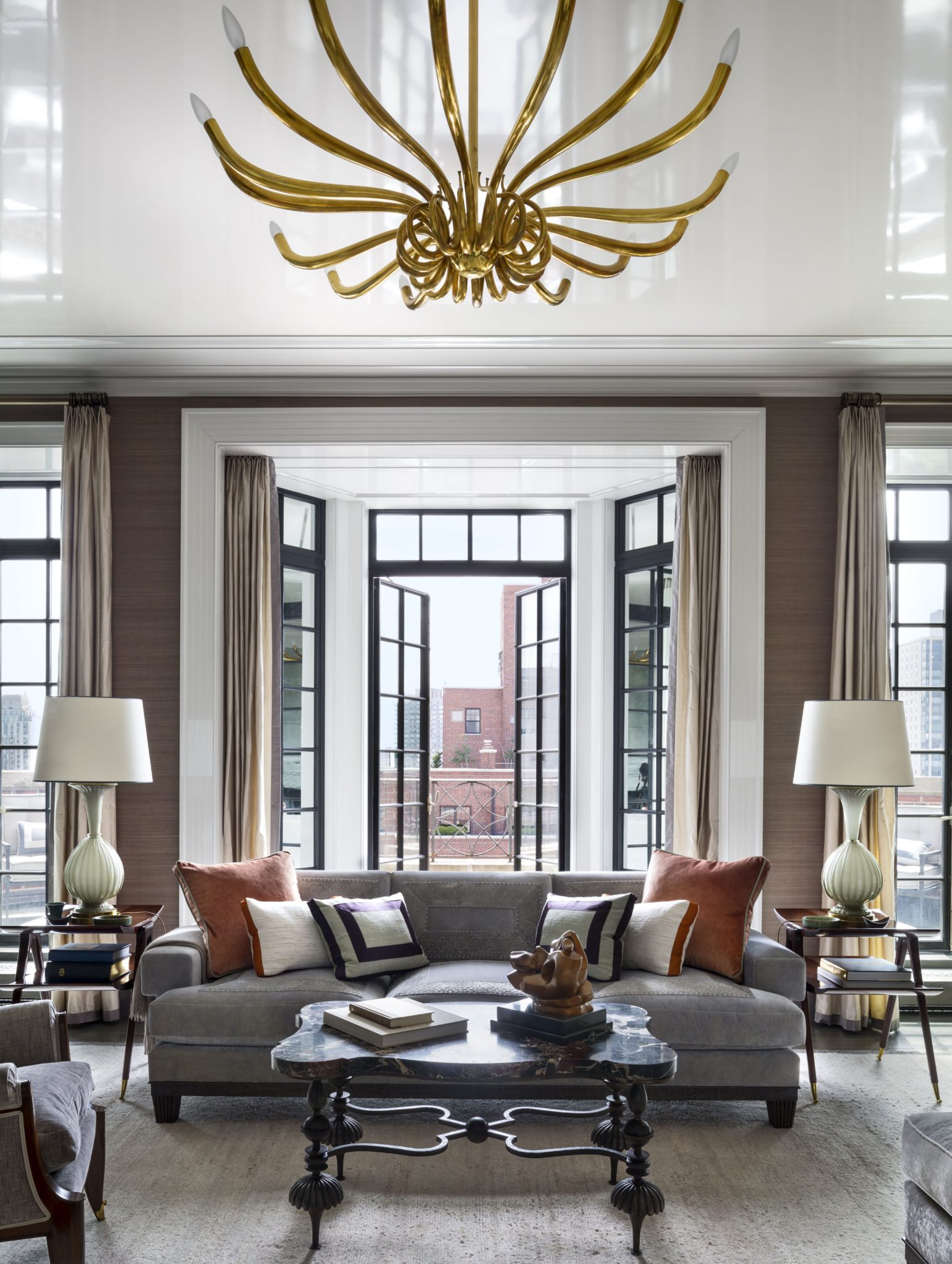 New French doors are flanked by mirrored sidelights. The sofa was custom made by Dune,the cocktail table is by Gilbert Poillerat and Serge Roche—purchased at auction—and the vintage chandelier is from H.M. Luther.