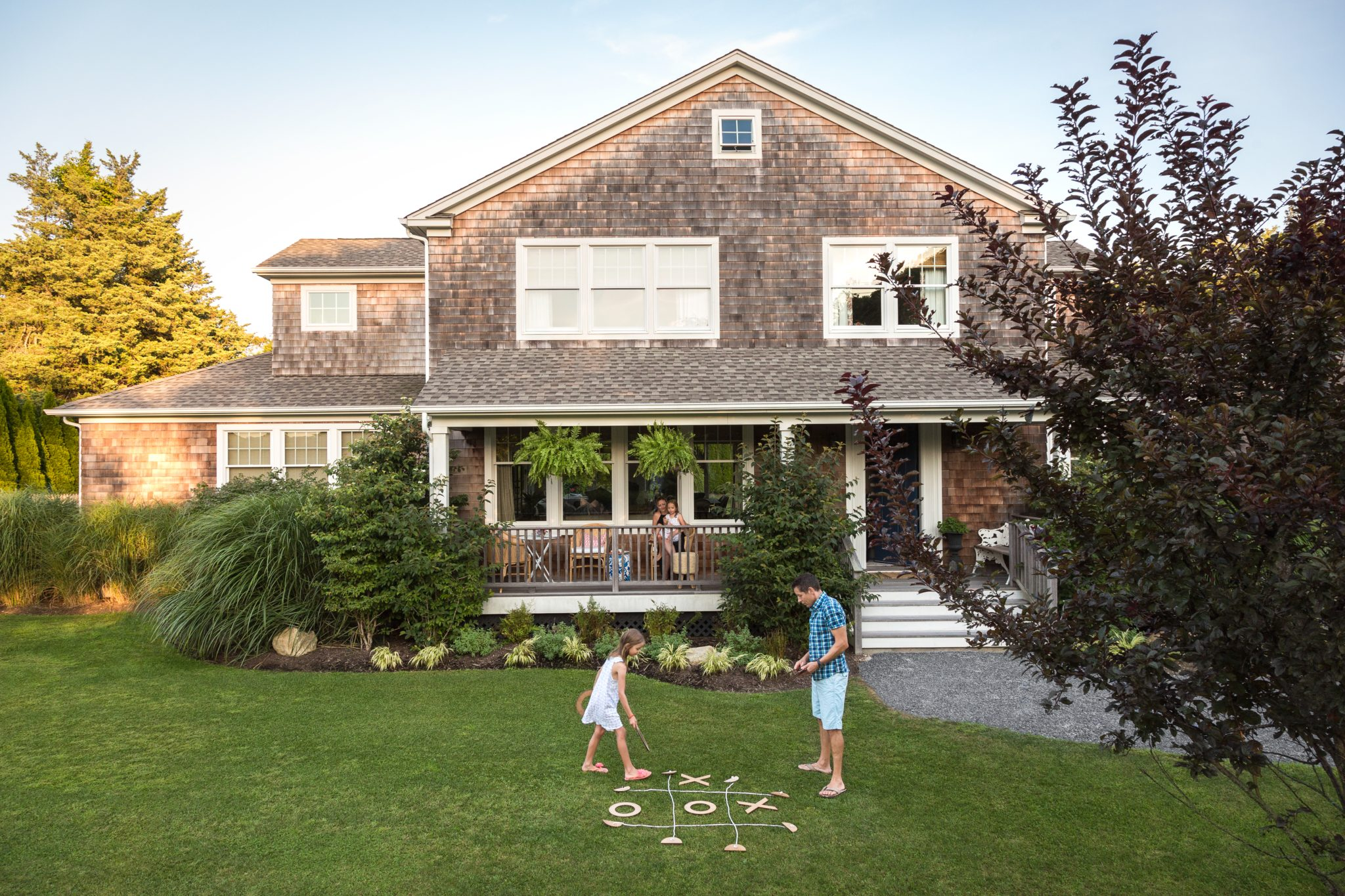 Front Porch in classic Hampton's shingle style weekend house by Bella Mancini Design