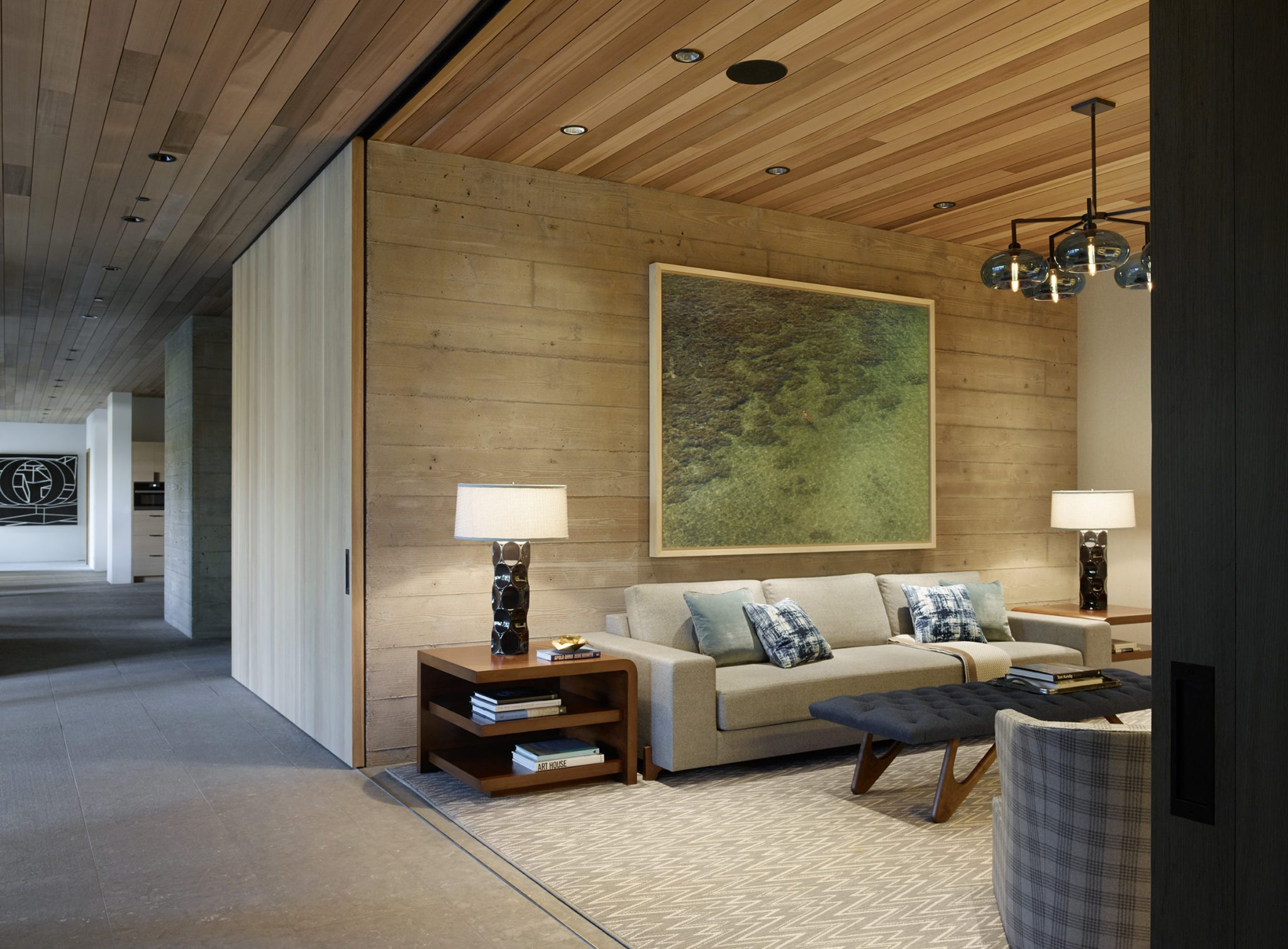 In the TV room, the sofa by Holly Hunt is upholstered in a Holland and Sherry fabric, the side tablesby Michael Berman are topped with lamps by Arteriors, the chandelier is by Niche Modern,and the photograph is by Richard Misrach.