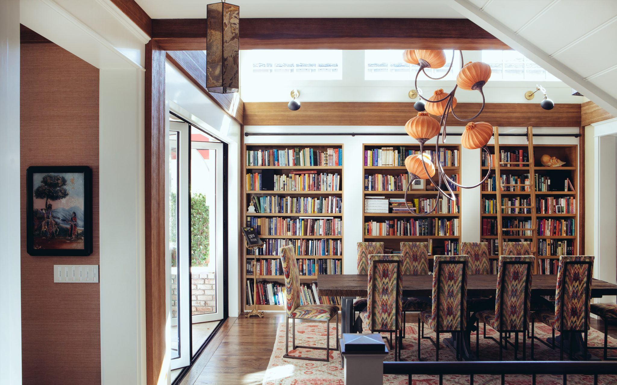 Sustainable cottage dining room with statement chandelier and library wall by Fergus Garber Young Architects