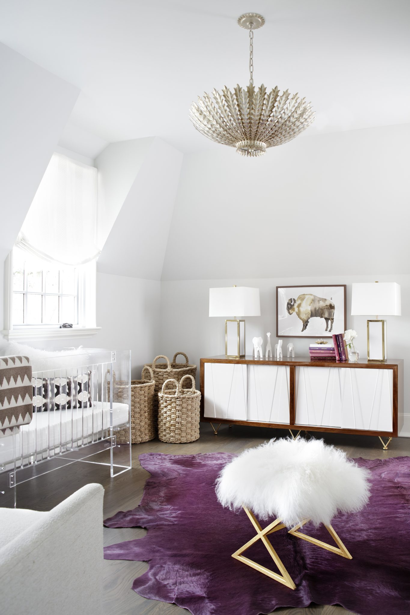 Comprising themid-century modern credenza, purple rug, and fur-topped stool, furnishings from Kellum & Company in Birmingham, Albama, provide the backbone of the nursery design. The overhead lighting fixture is from Visual Comfort, and the baskets are from Scott's Antique Markets in Atlanta.