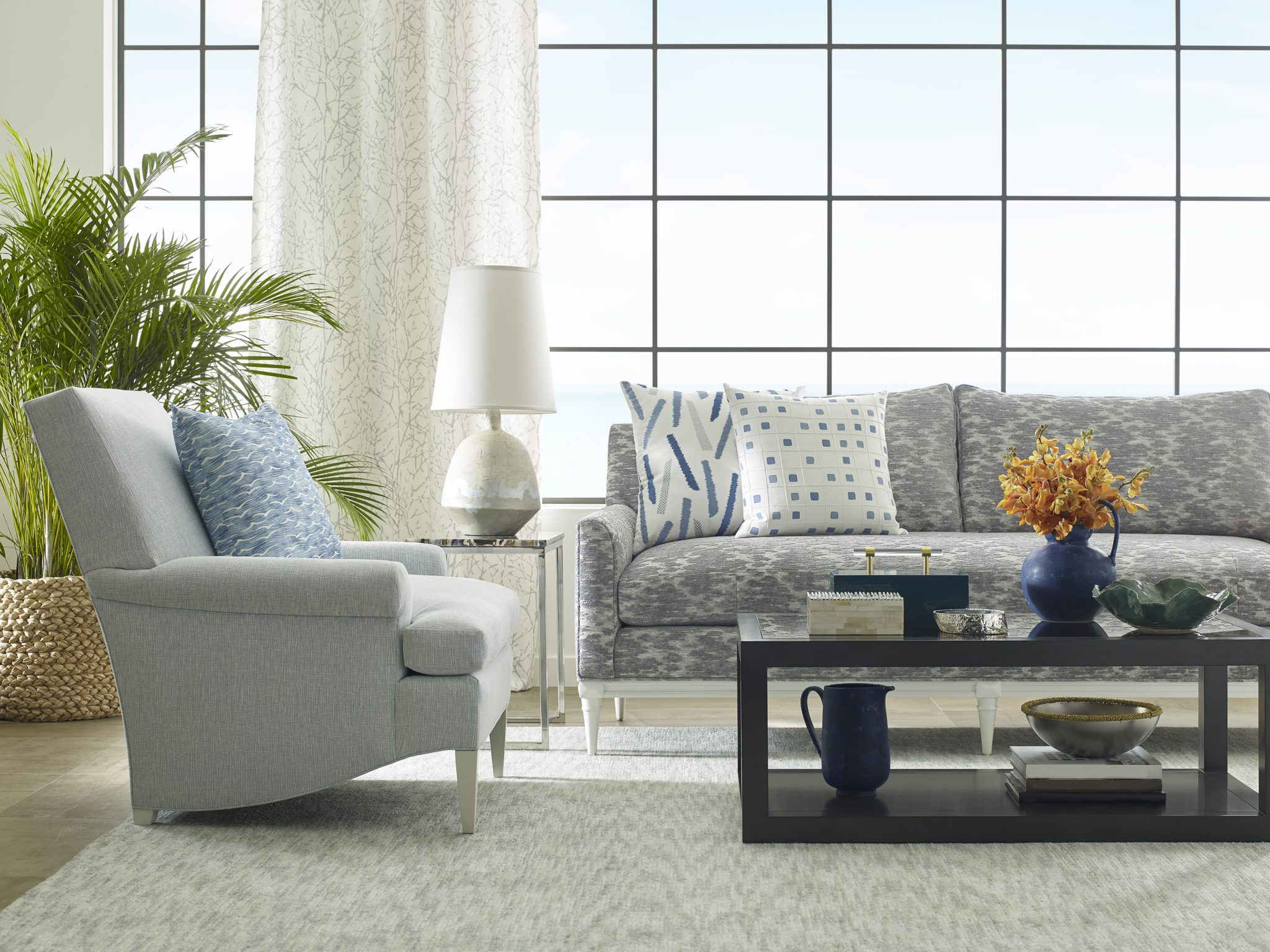 In this living room scene, the Tatsworth sofa is shown in the Immersive in Pewter fabric, with pillows covered (left to right) in Tramonto in Ocean and Gridwork in Ocean. The armchair is the Dorset chair, in the Mysto in Pacific fabric; the pillow is in Angelus in Pacific. In the background, the curtains are Branches in Pewter; the side table is the Arvada side table, with the Maria lamp atop it. In the foreground, the Millbrook cocktail table is shown, decorated with the Yuma box, Foster presentation box, Noemi polished agate bowl, Anson vase, Linden bowl, Beatrice vase, and Mauna bowl.