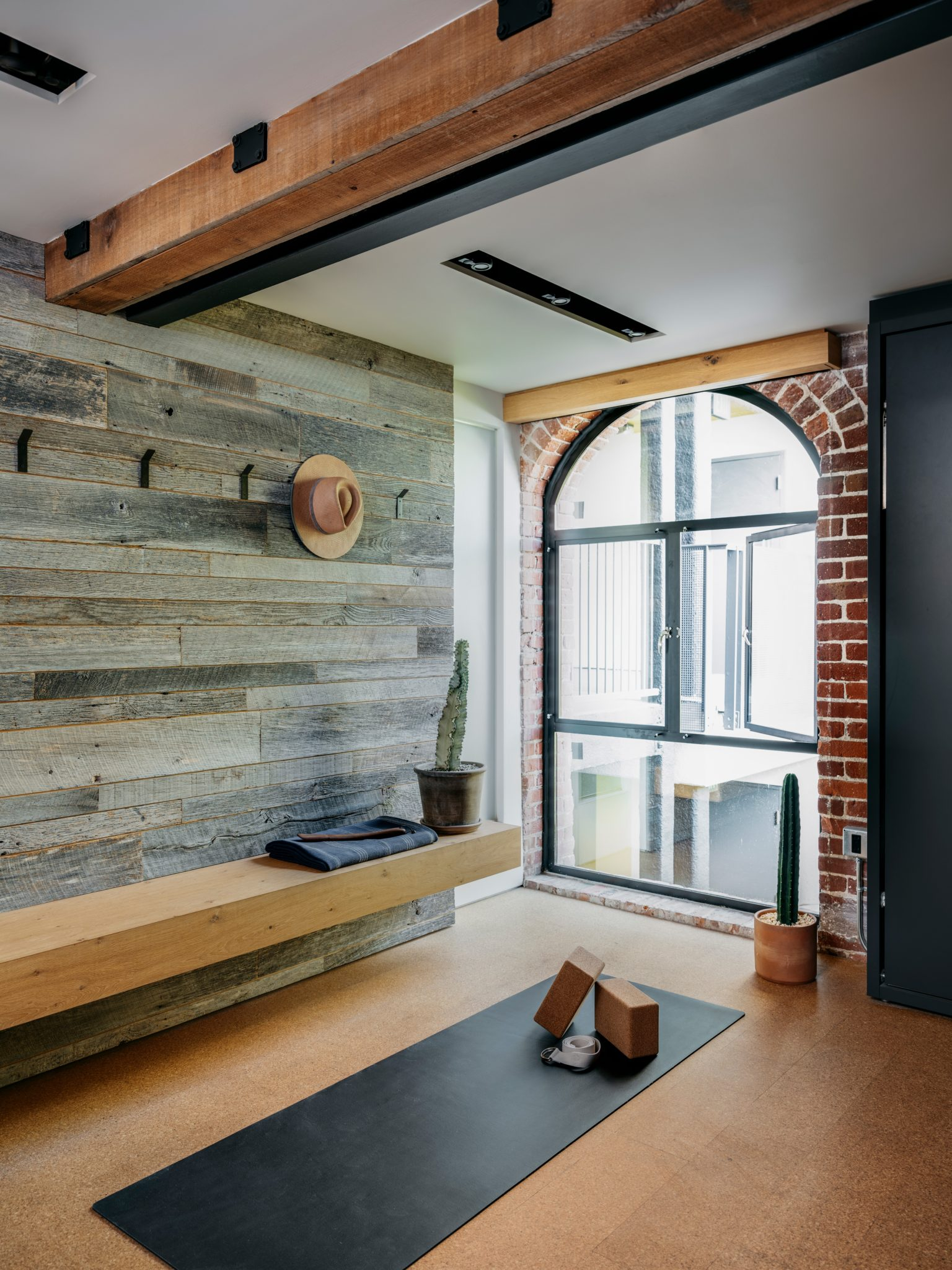 Murdock included a half-inch thick cork floorto provide extra cushioning for the clients' workouts. The white oak bench here was custom-designed by MODTAGE Design.