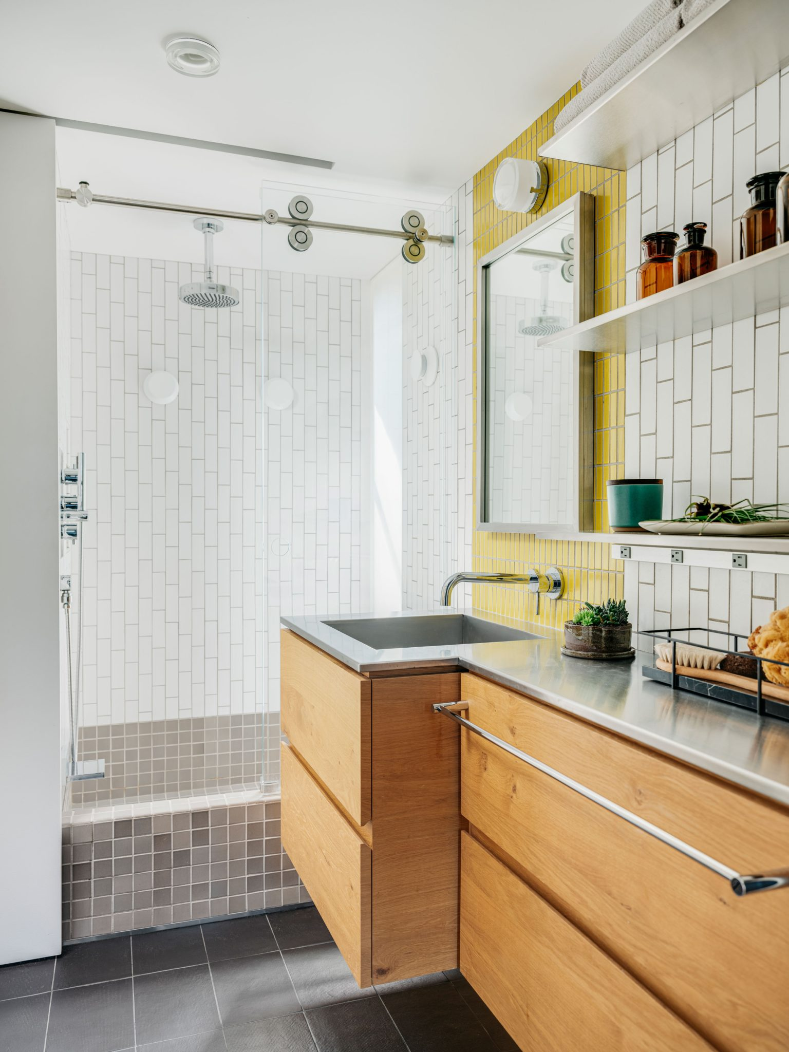 Custom glass sidelightsin the guest bathallow extra light to enter into the space. Stainless steel countertops are paired with awhite oak vanity.The floor tiles were designed by Patricia Urquiola, and the wall tiles are from Heath Ceramics; the faucets are from Blu Bathworks.