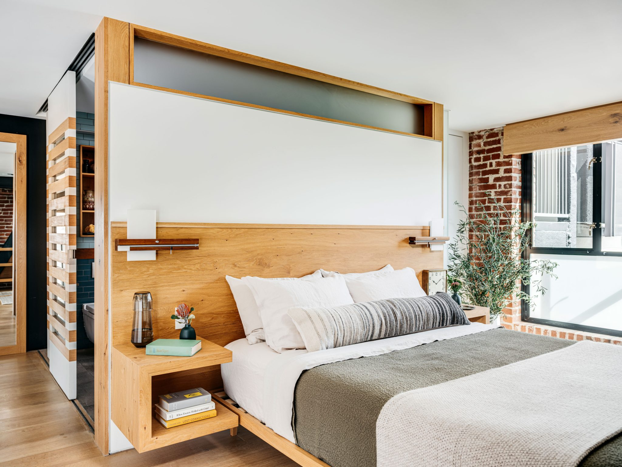In the master bedroom, Murdock designed a custom white oak headboard with a platform and integrated floating nightstands for the clients.