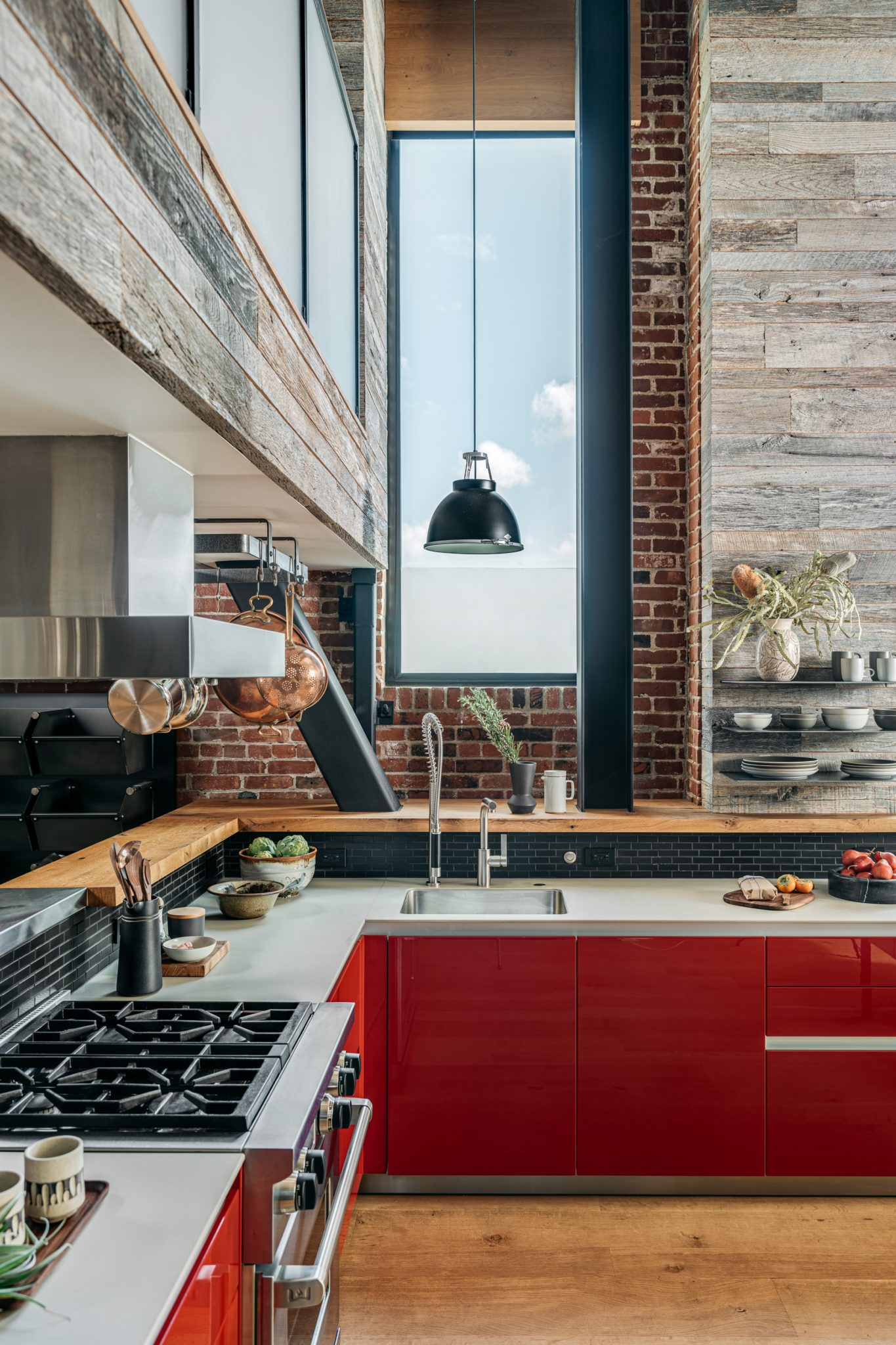 The red lacquered kitchen cabinetry from Bulthaup makes a statement; the countertops are also from Bulthaup. Reclaimed barn siding wraps around the kitchen area, and white oak fascias subtly conceal the window shades.