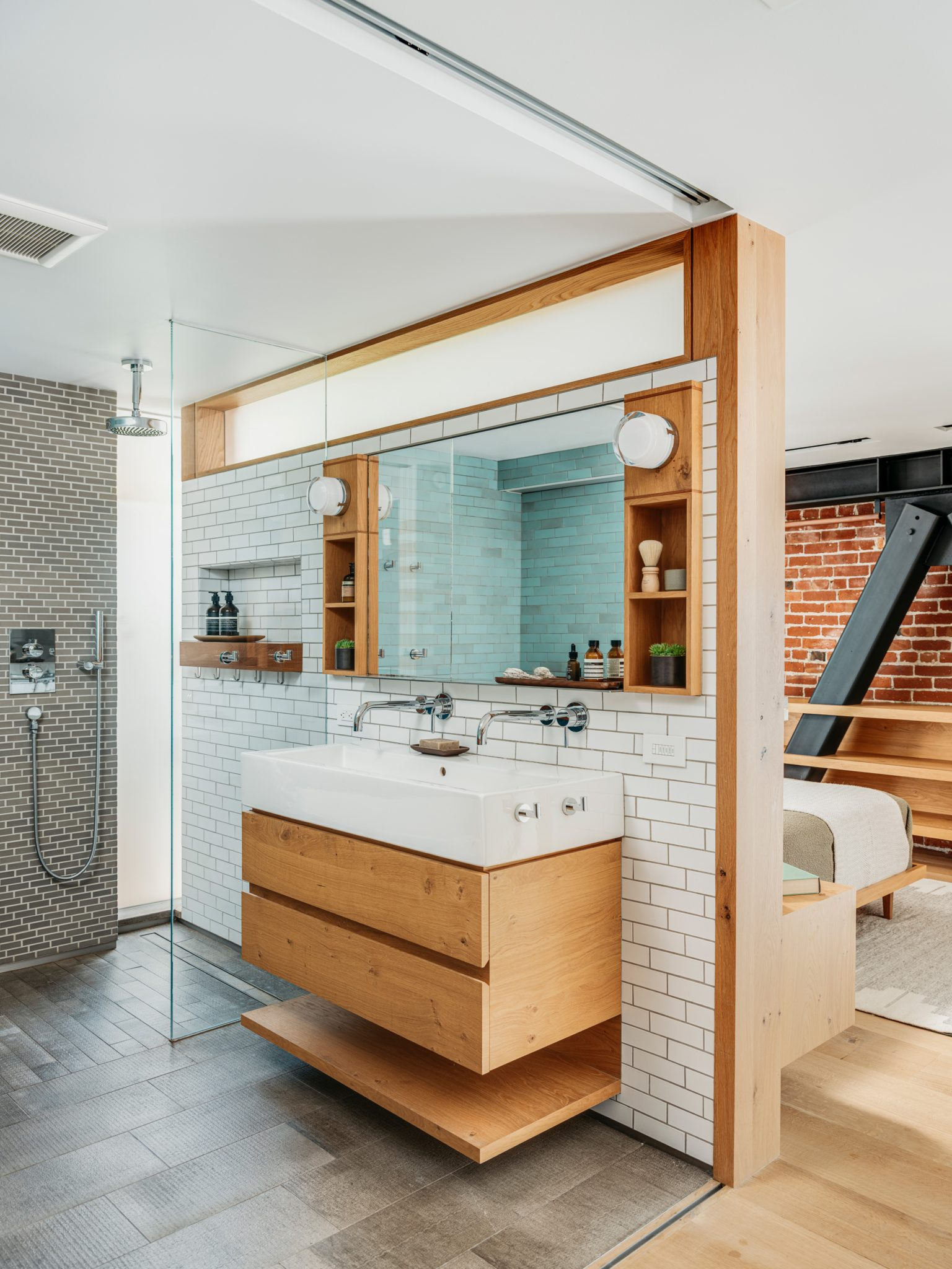 Heath Ceramics tile decorates the walls. The custom vanity was crafted from white oak, the sink is from La Cava, and the faucets are from Blu Bathworks. The curbless shower is an impactful aspect of the design.