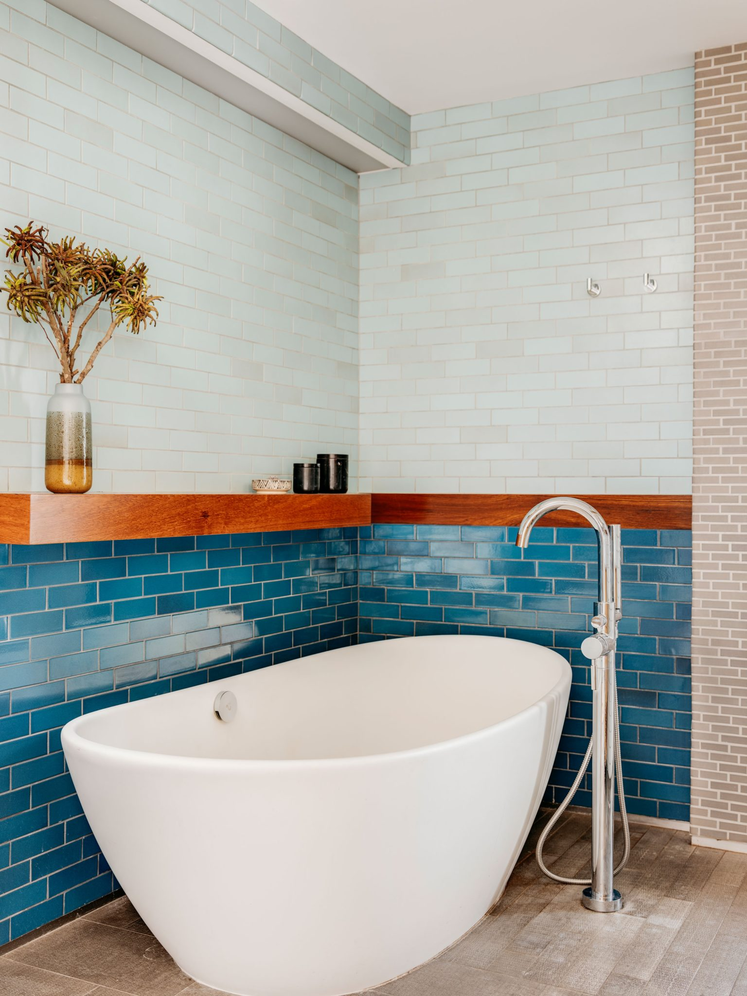 The freestanding tub is set upon stone flooring. Carefully placed custom shelving leans out over the tub.