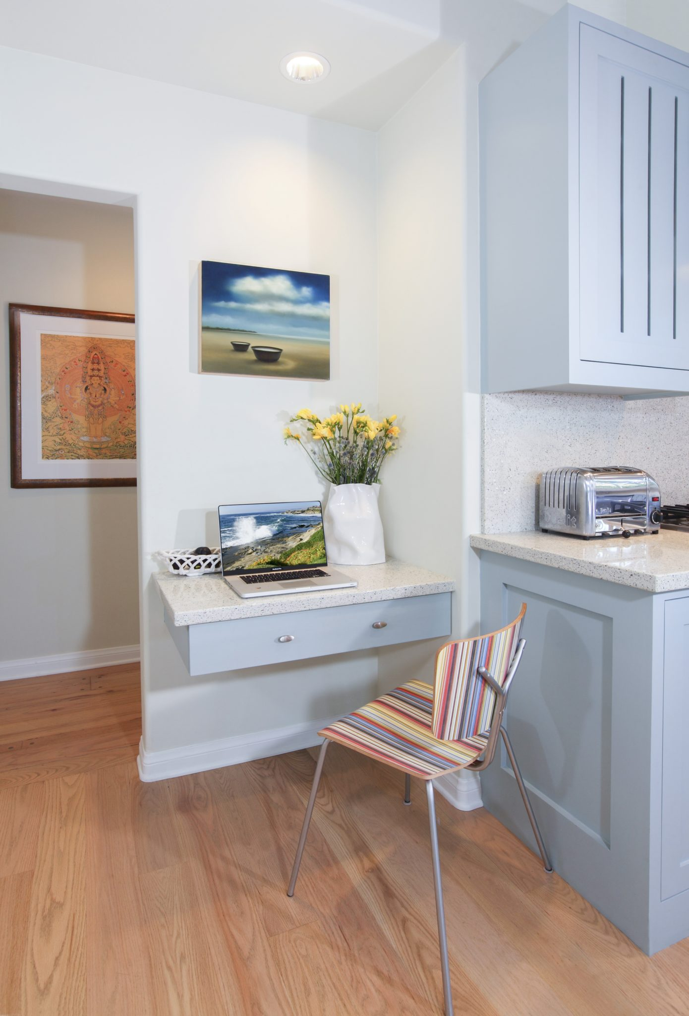 The kitchen office nook with floating desk drawer provides a tidy reading space. by Sarah Barnard Design