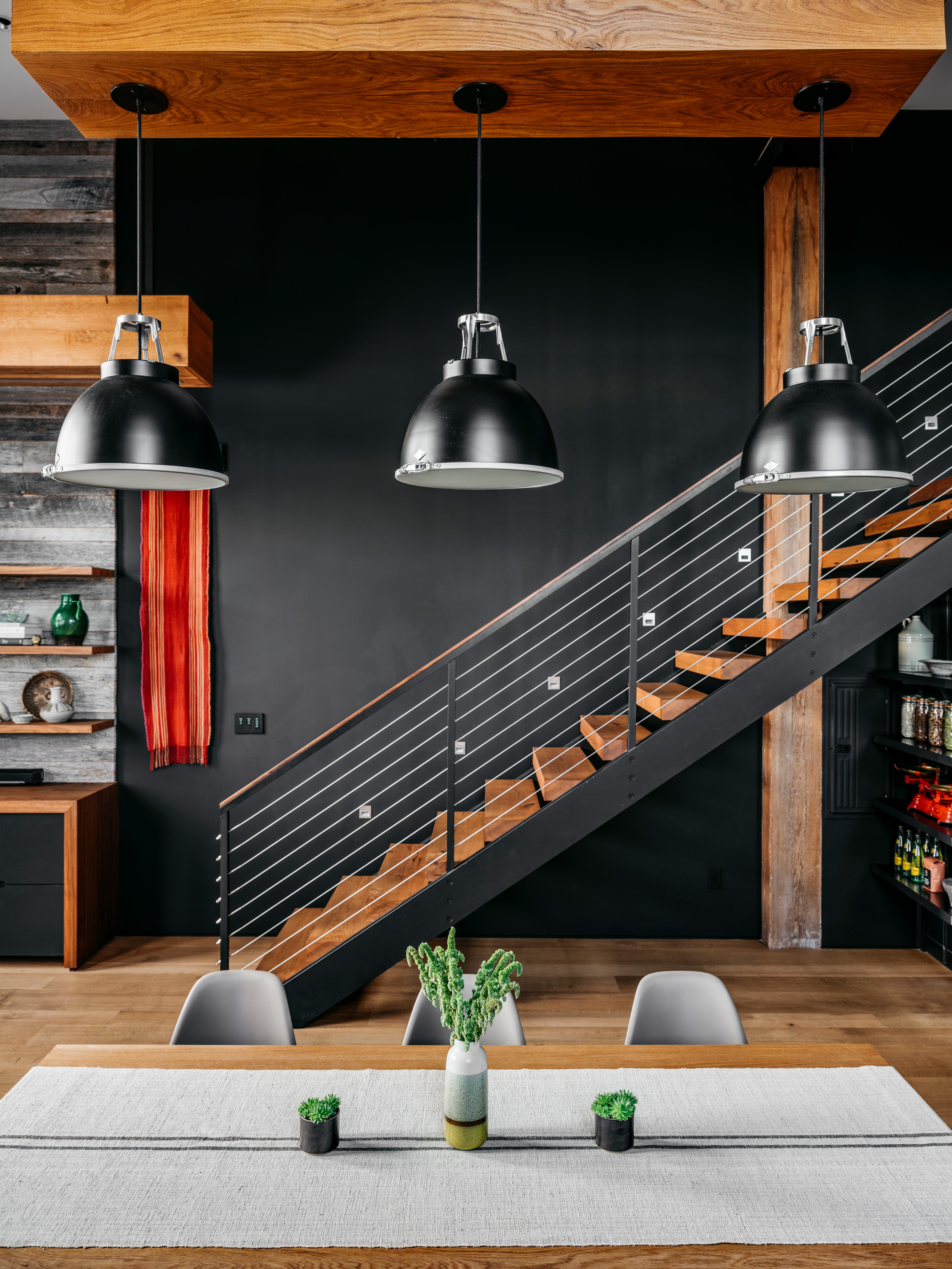 Industrial-style pendant lights are suspended over the custom dining table. The stairs in the background were custom designed by Murdock.