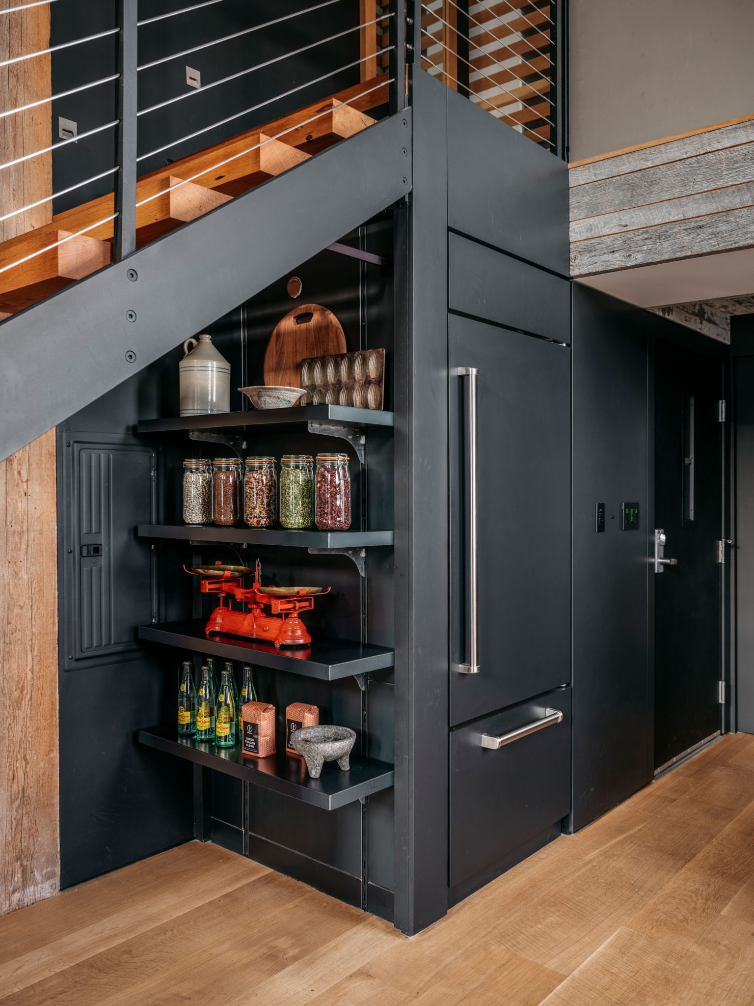 Under the stairs, this hidden shelving was also custom designed byMODTAGE Design.